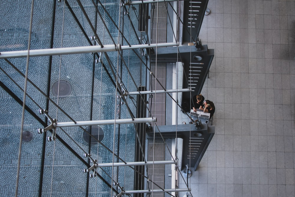 aerial photography of man and woman sitting near gray metal pillars