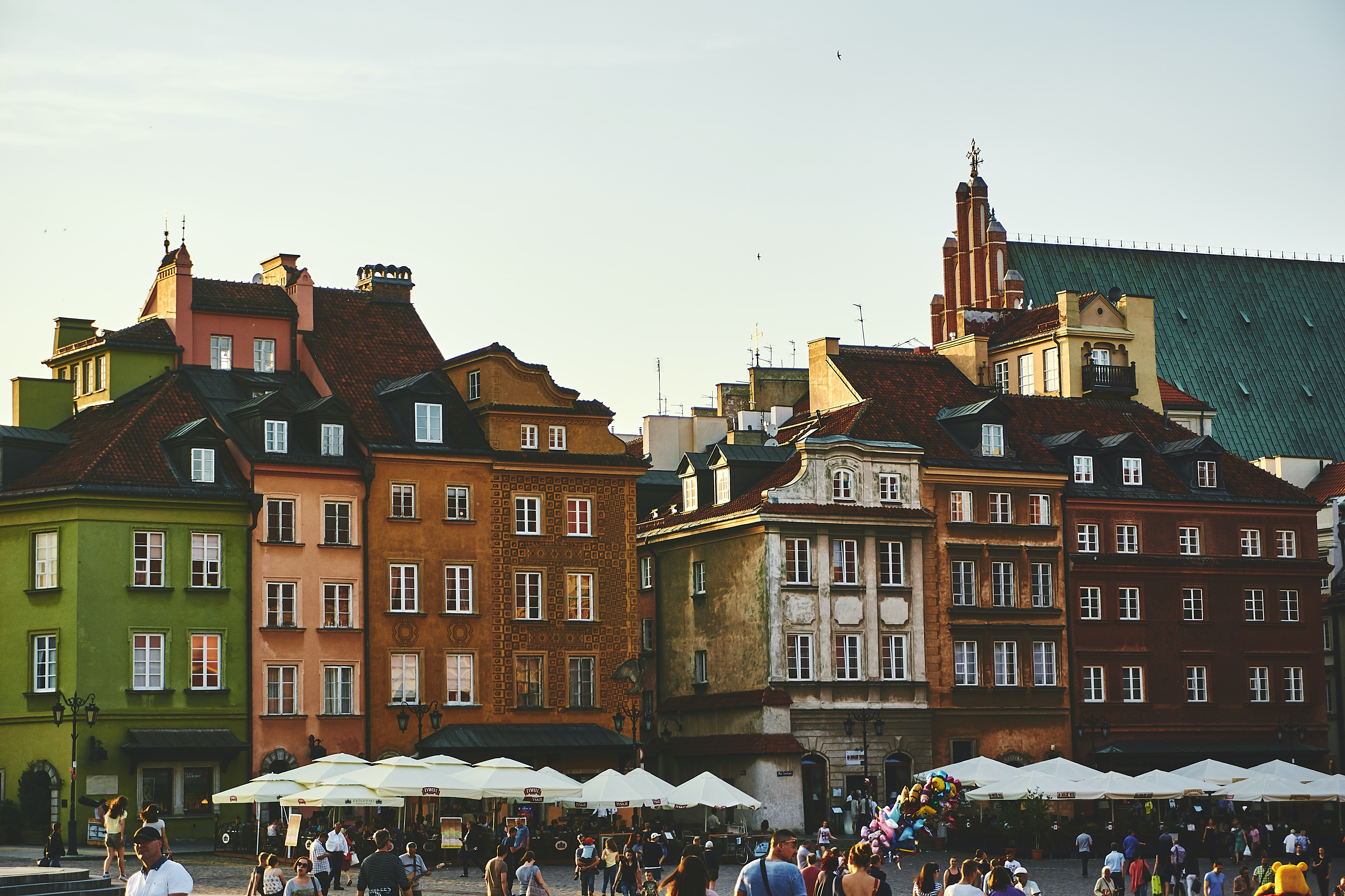 Tourists strolling near quaint tenement houses in the Castle Square in Warsaw