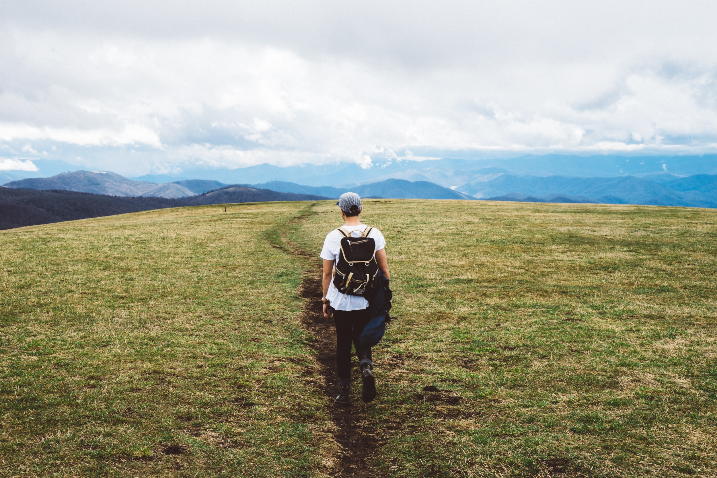 Man wearing a hat and backpack hikes away from the camera in green grass, toward mountains