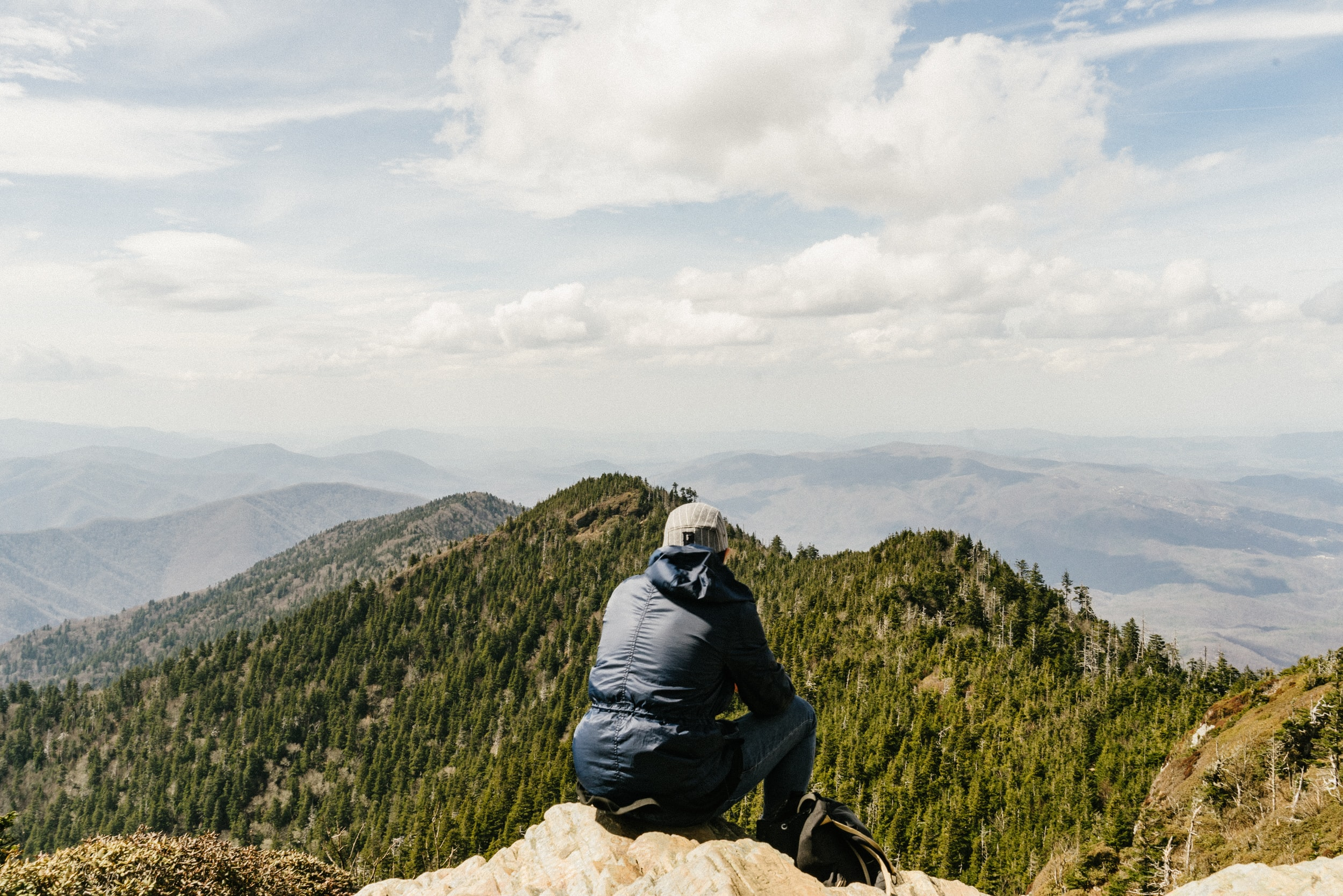 man sitting on mountain in front of trees under cloudy sky