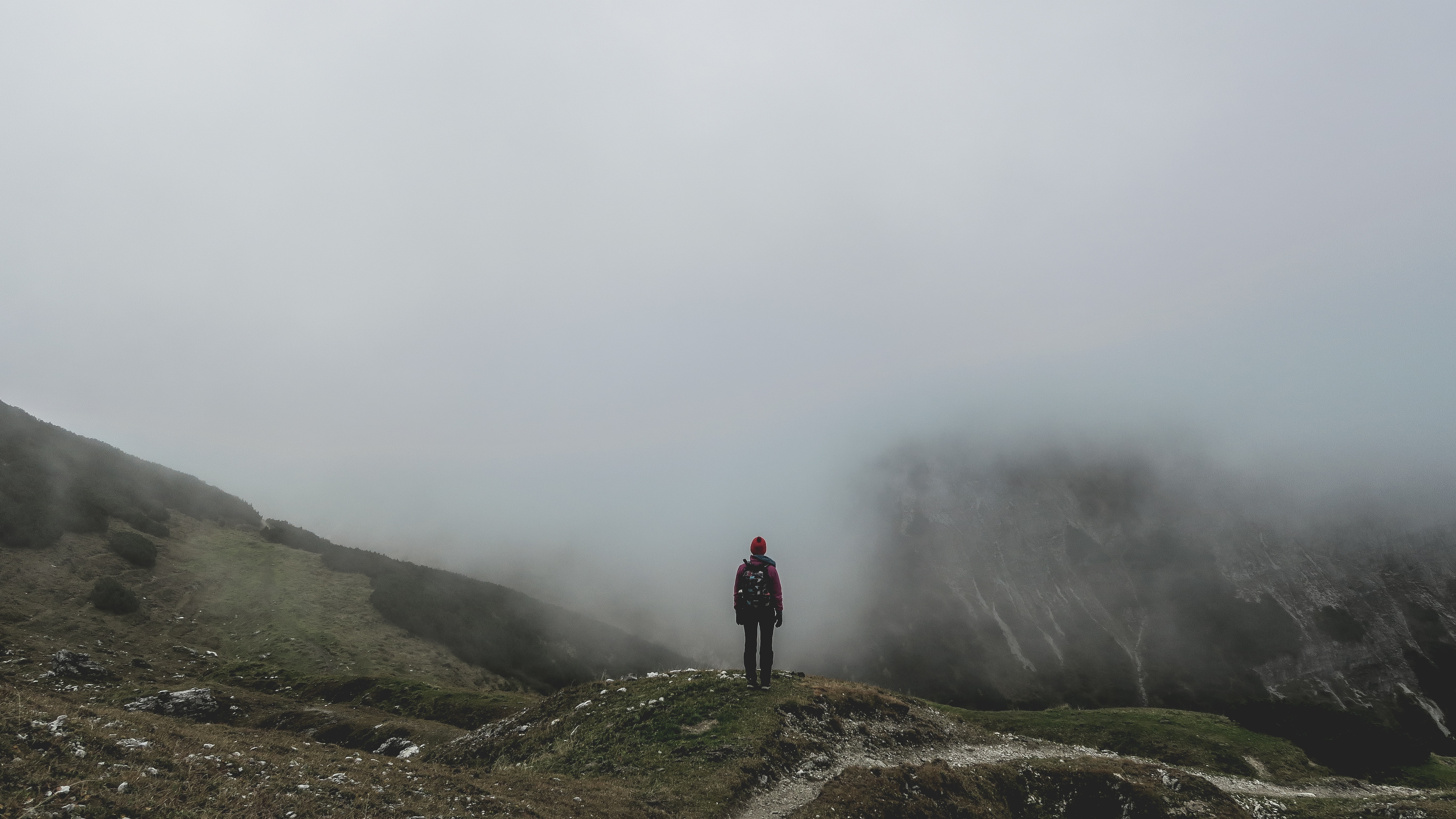 Hiker looks out at foggy mountains on a small rocky hill