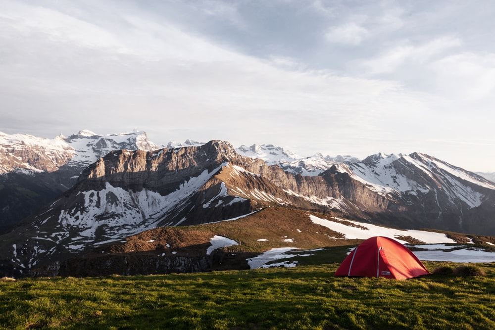 red tent on grass field beside ice capped mountain nature photography