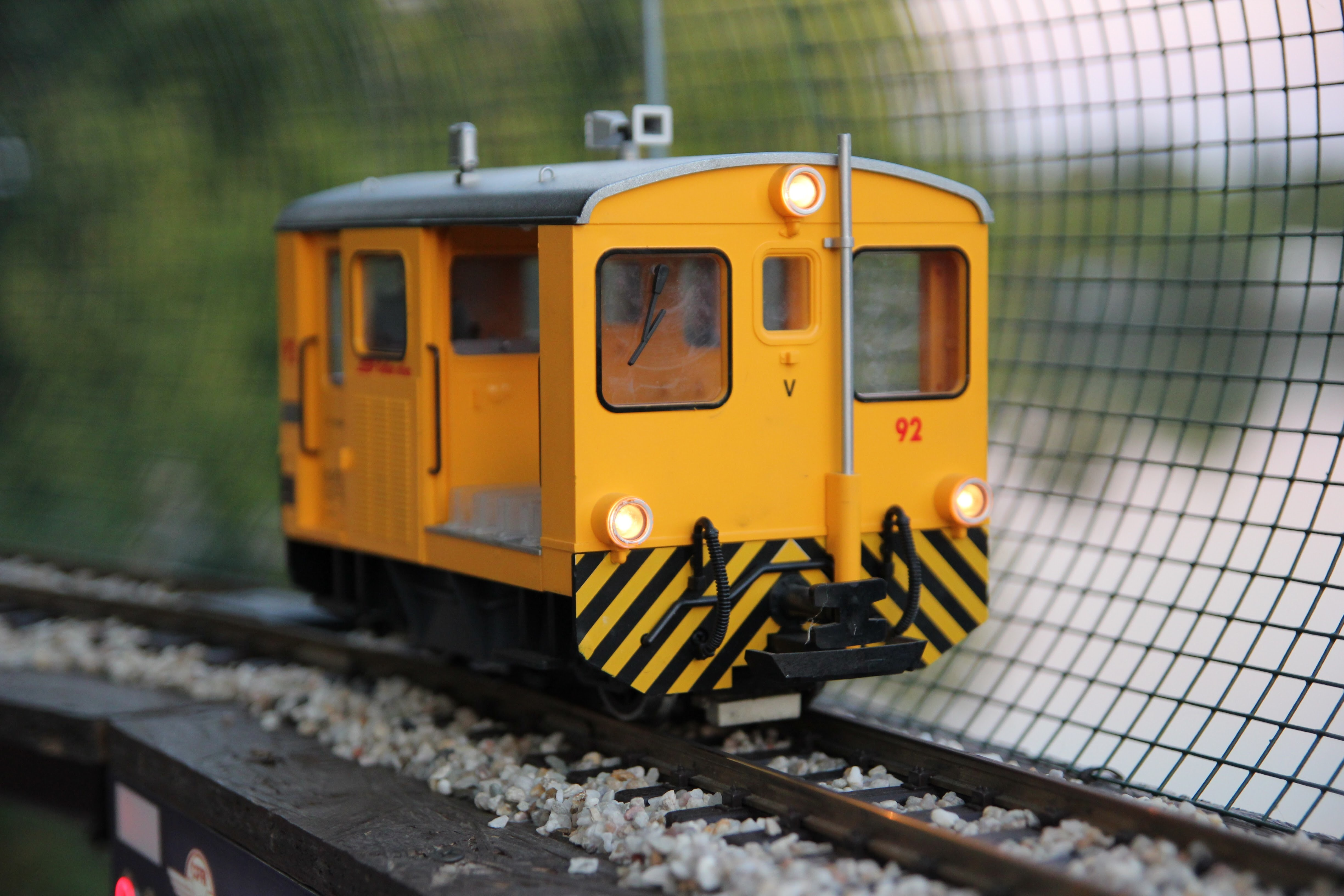 Yellow miniature railcar on a track with gravel and controls besides a wire fence
