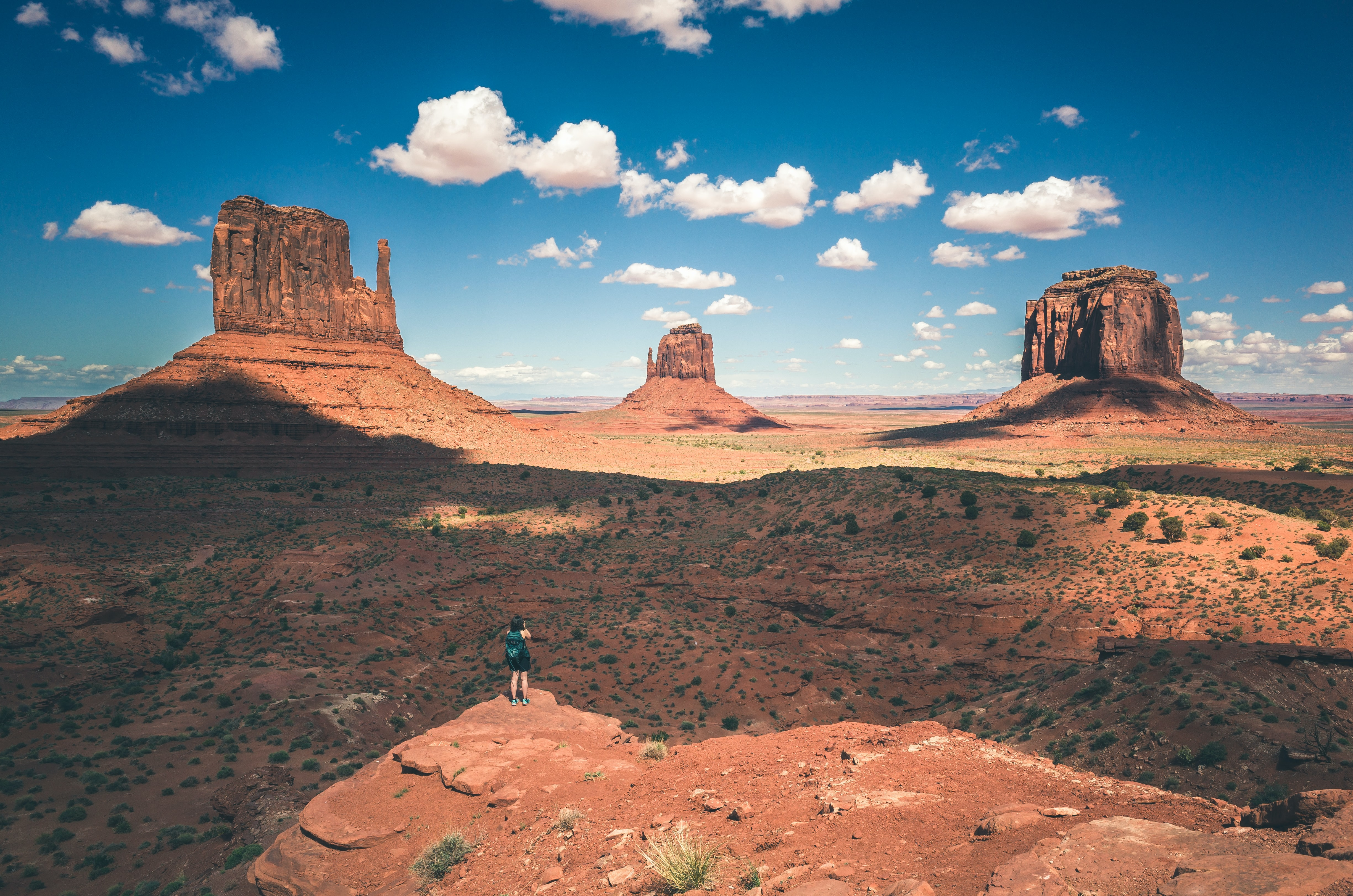 Hiker stands atop a peak of a rock formation in the desert of Oljato-Monument Valley