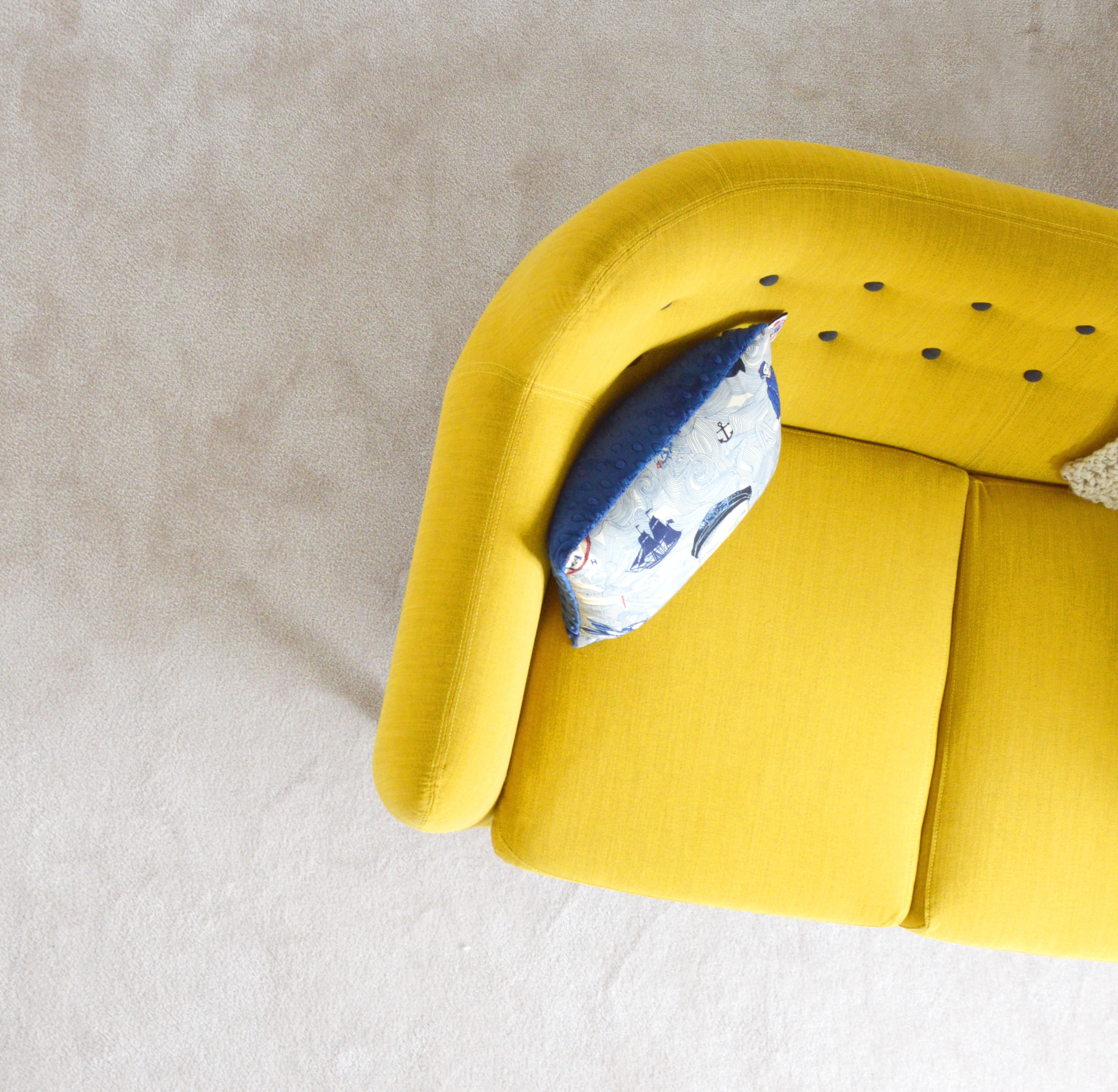 A yellow sofa with blue cushions in France