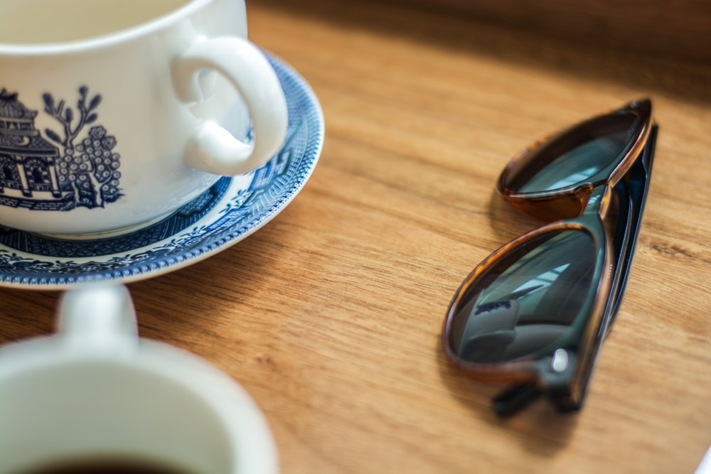 black framed sunglasses beside mug and saucer