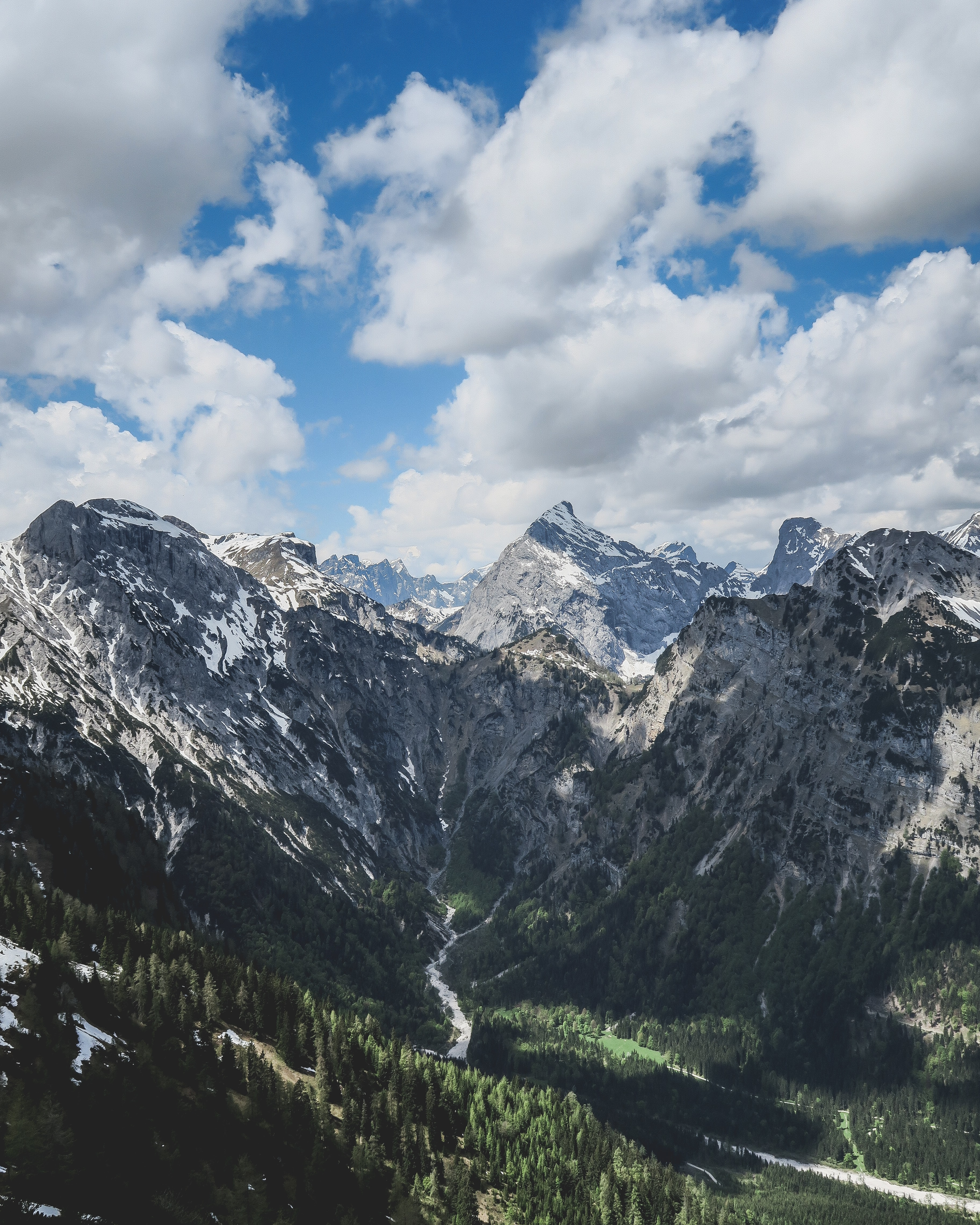 River flowing from the snowy peaks of Pertisau into the pine valley on a cloudy day