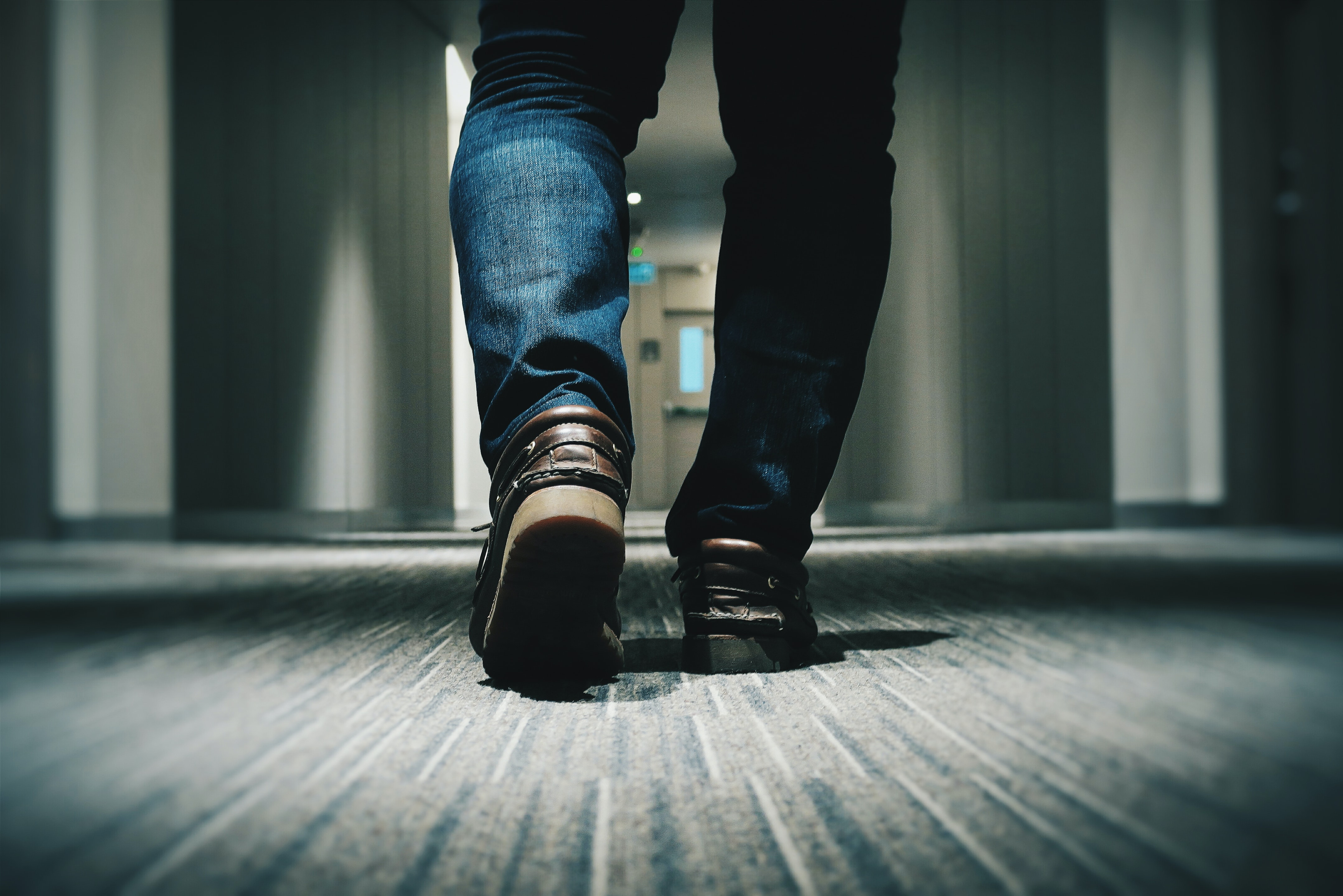 A low shot of a person in jeans walking through a hotel corridor