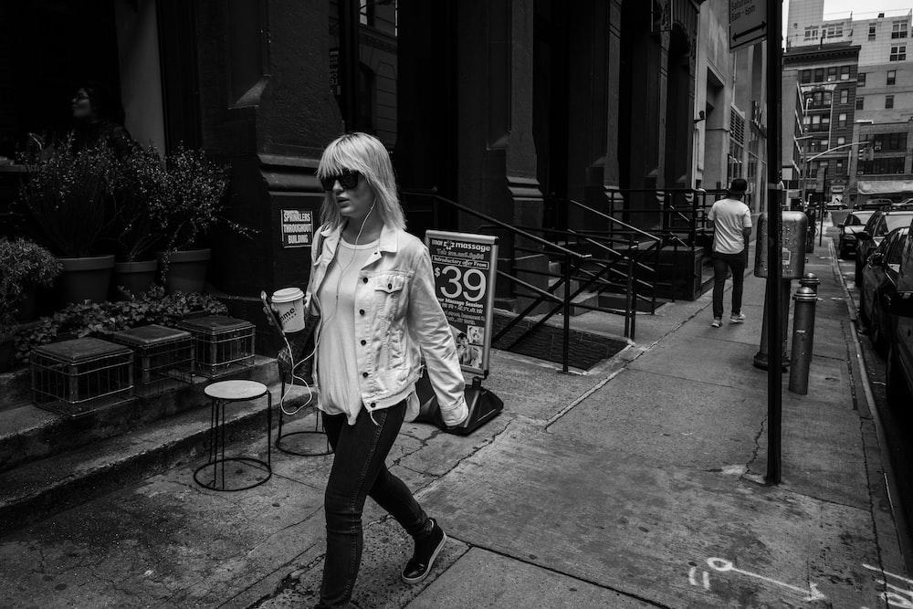 woman walking on pathway near concrete building