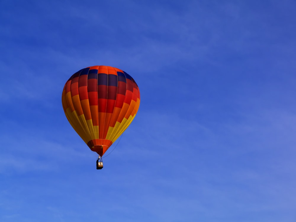 photo of red hot air balloon on sky