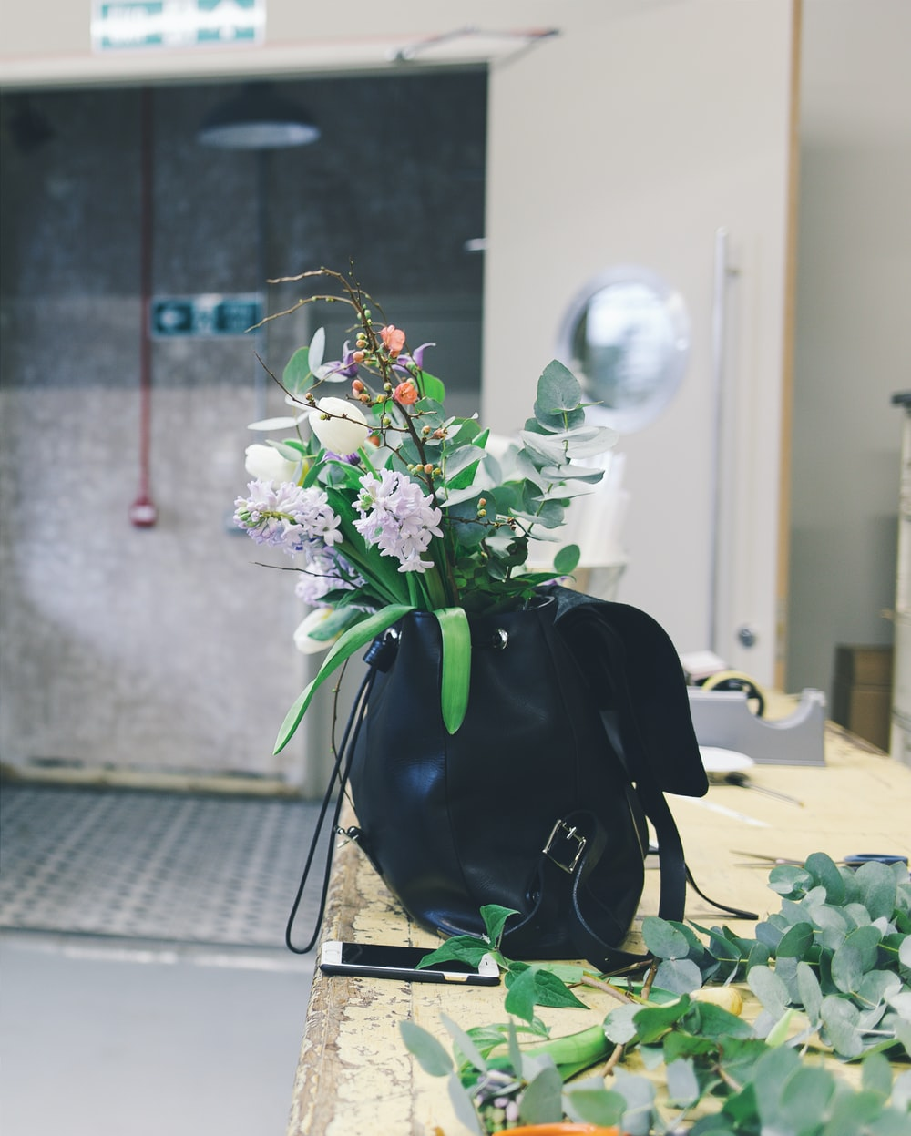 white and orange flowers in black leather backpack
