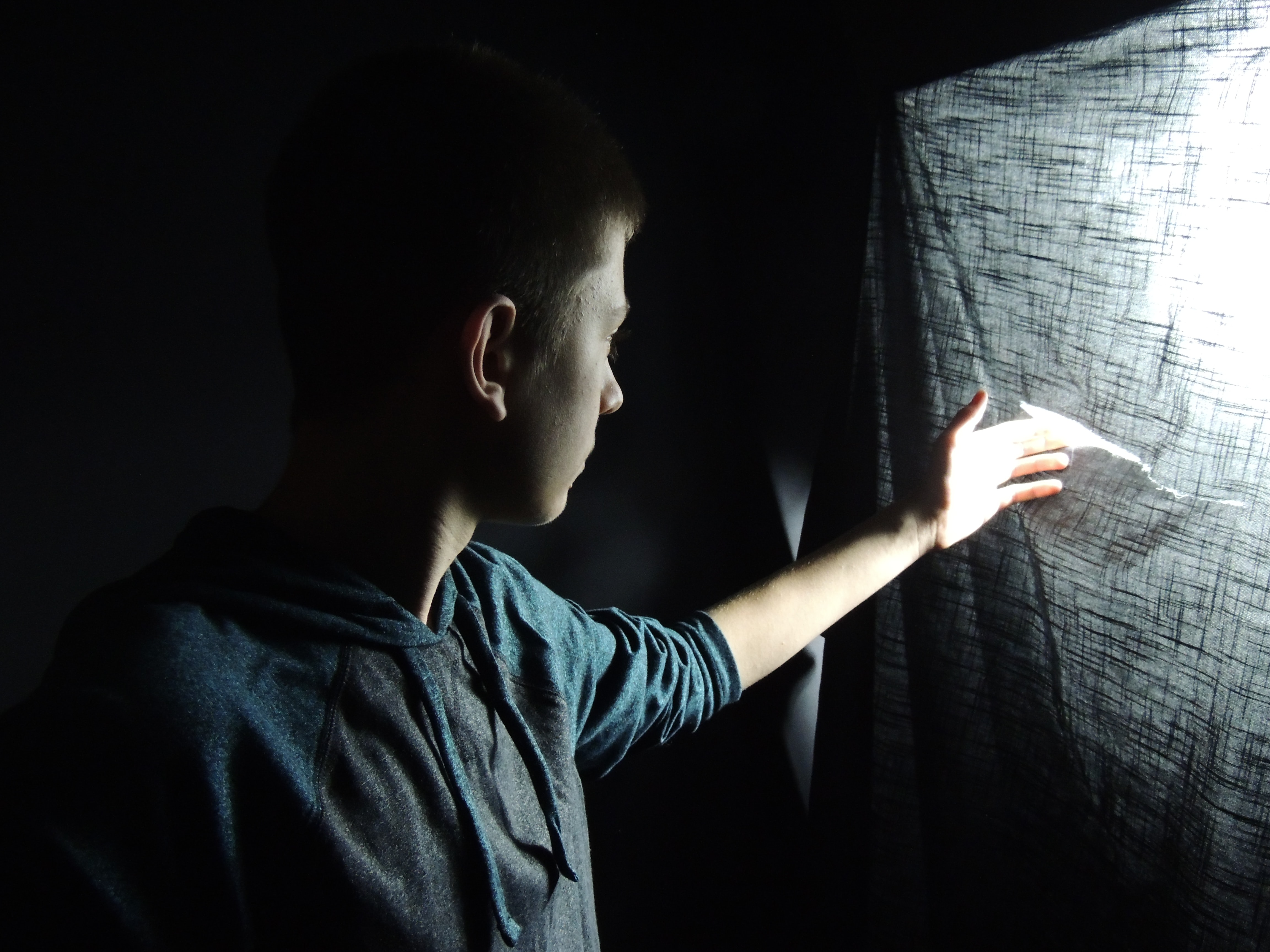 A boy touches the tear of a piece of cloth where light is coming in.