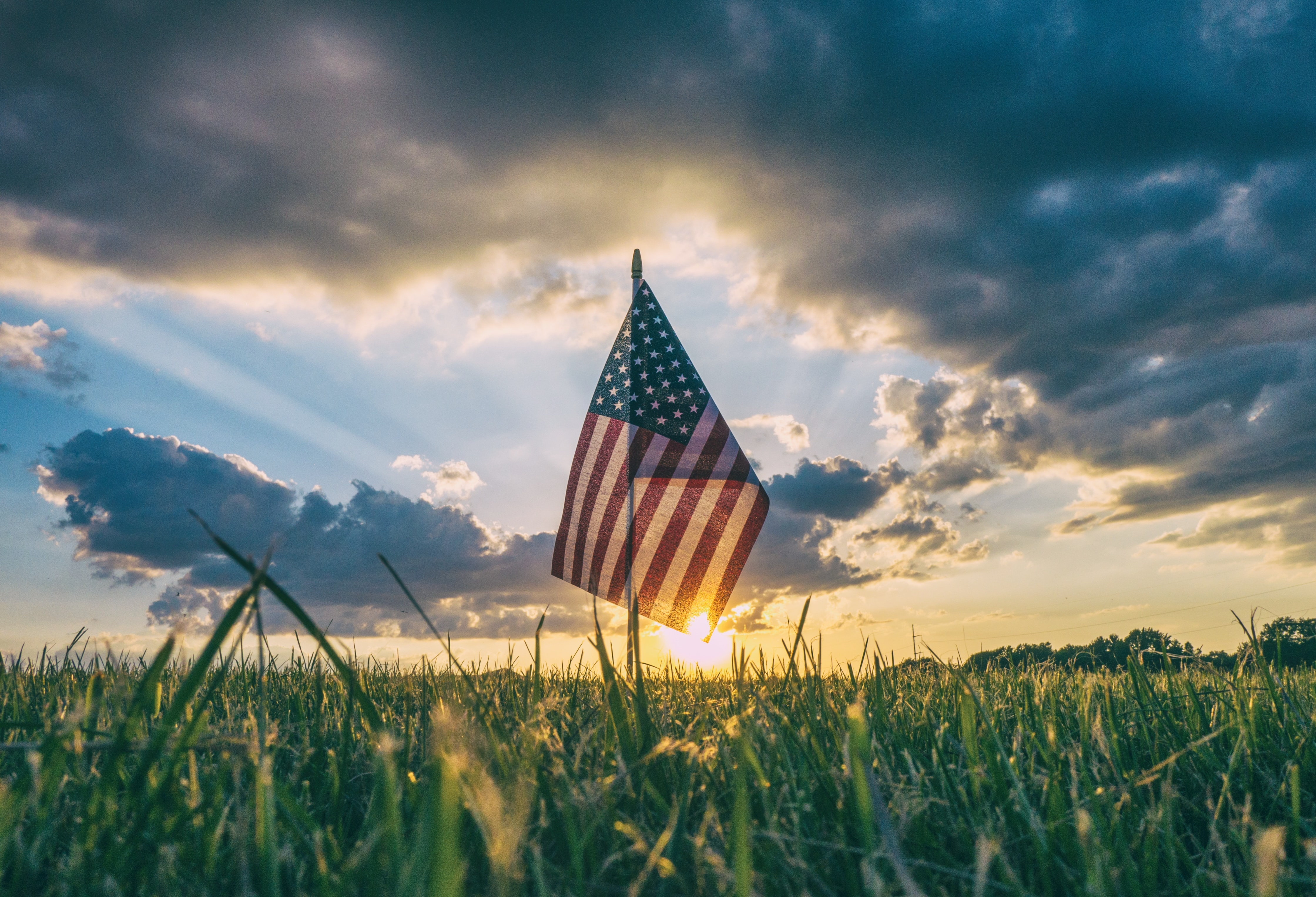 The flag of America stands in the grass with looming sunnset on 4th of July
