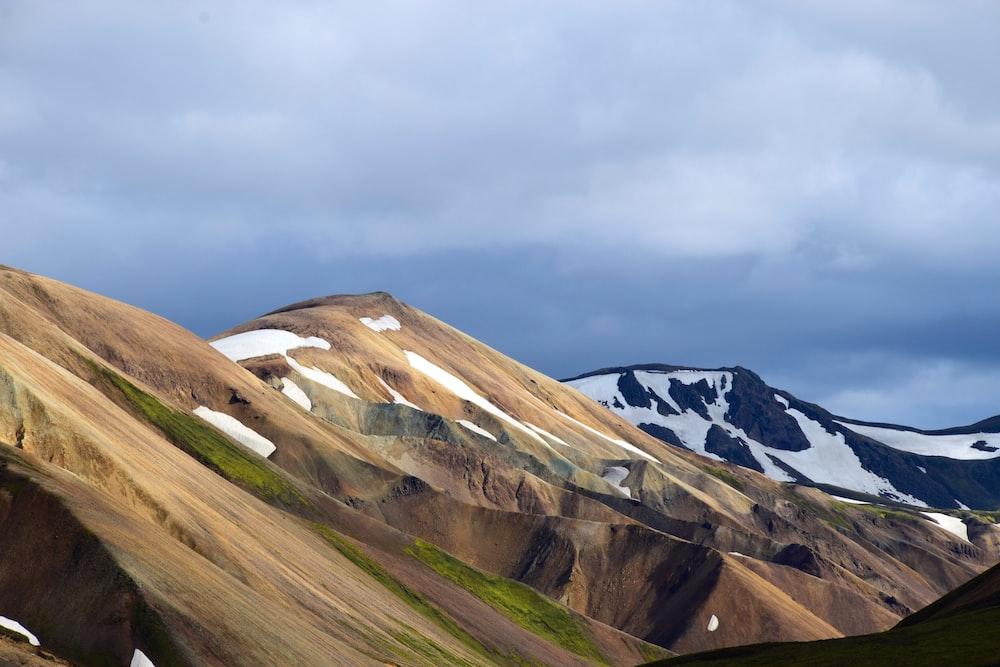 brown hill under white clouds
