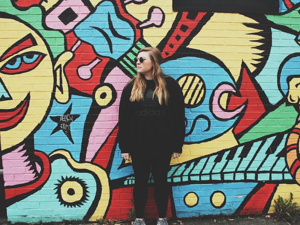 woman standing beside wall with graffiti