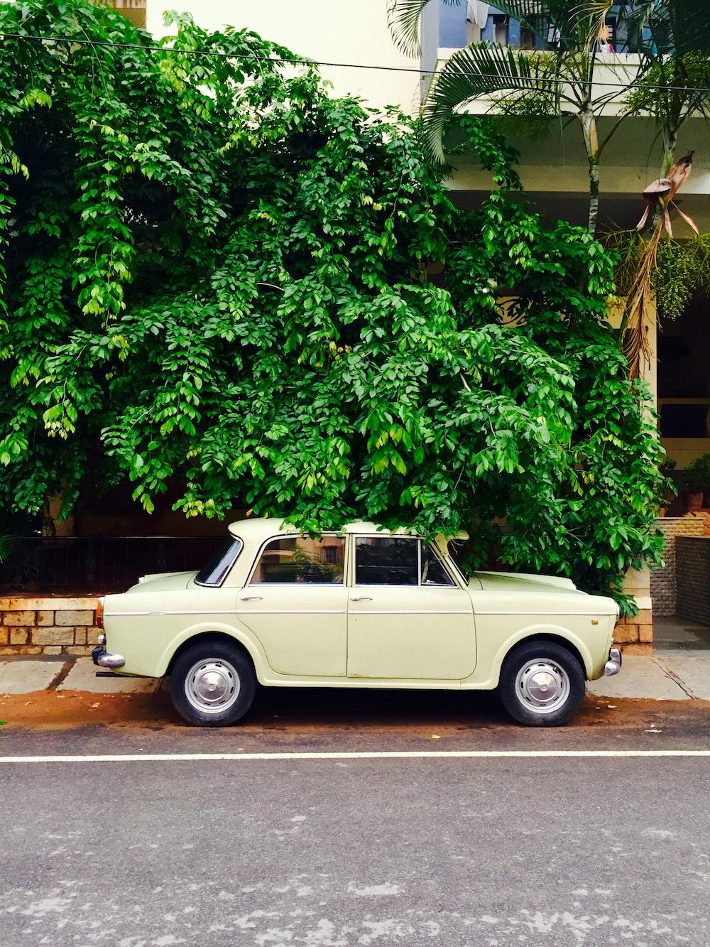 classic white sedan parked on sidewalk near white building