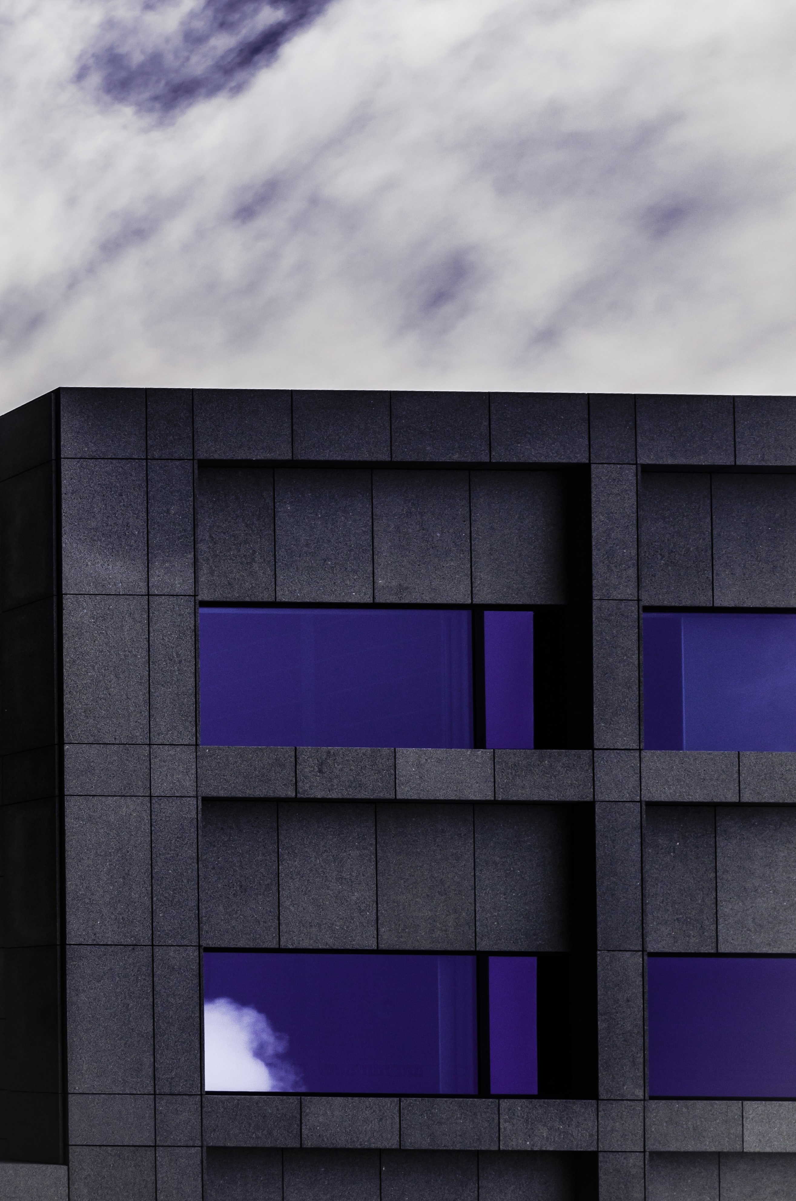 A black facade with dark blue sky reflected in the building's windows