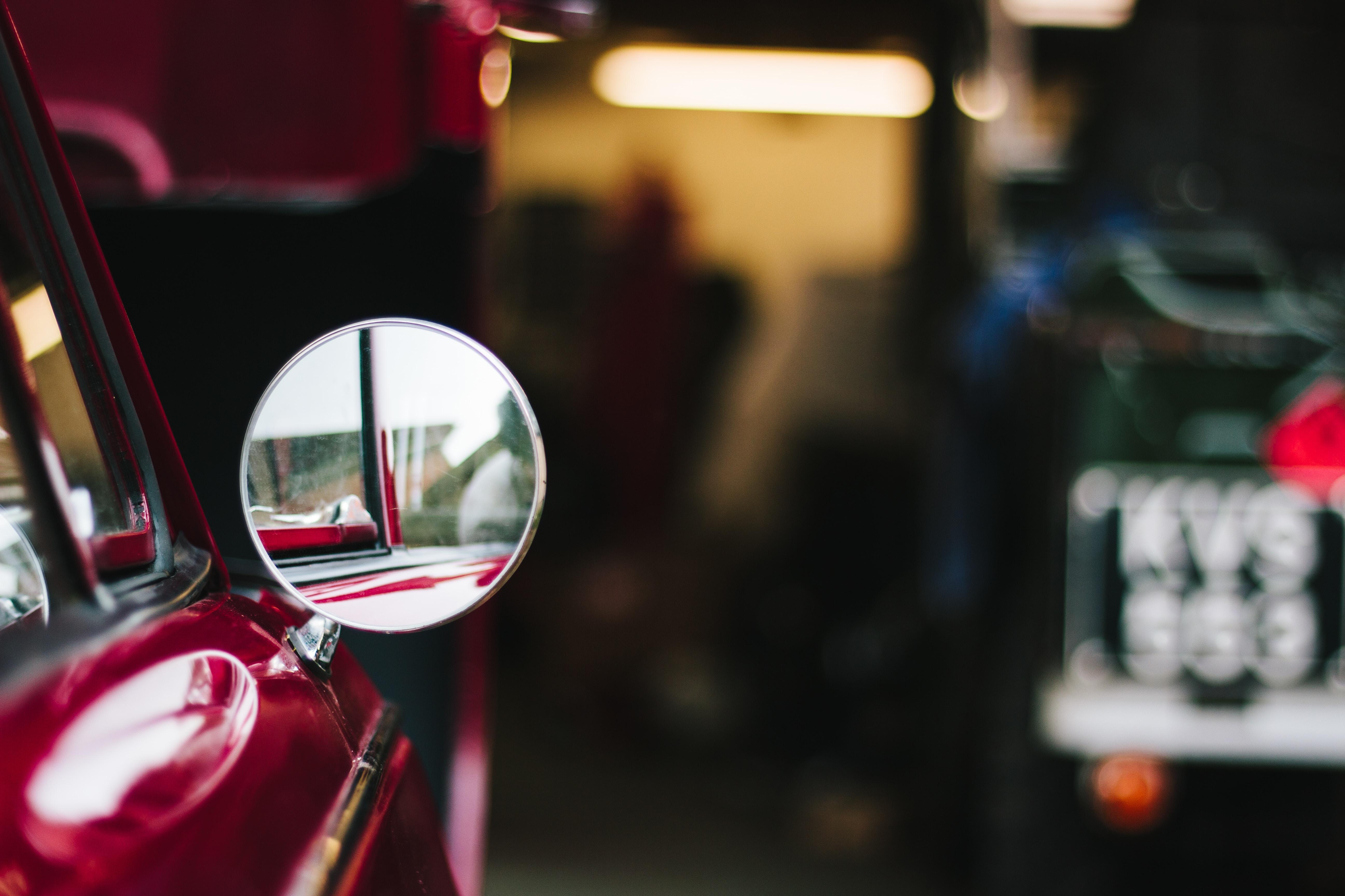 Close up of vintage circular car wing mirror on red car