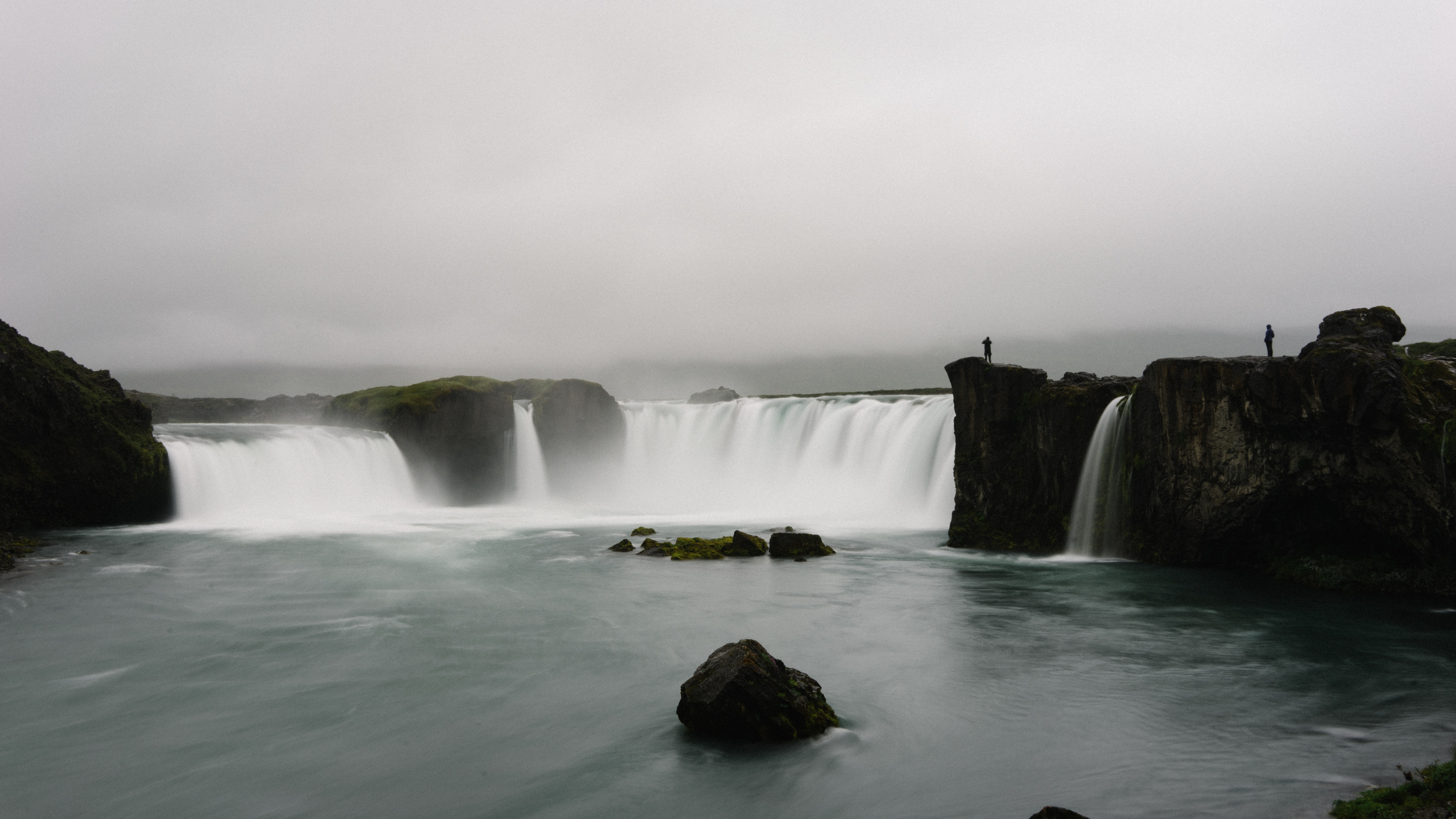 A gray image capturing two waterfalls streaming into a pool of water