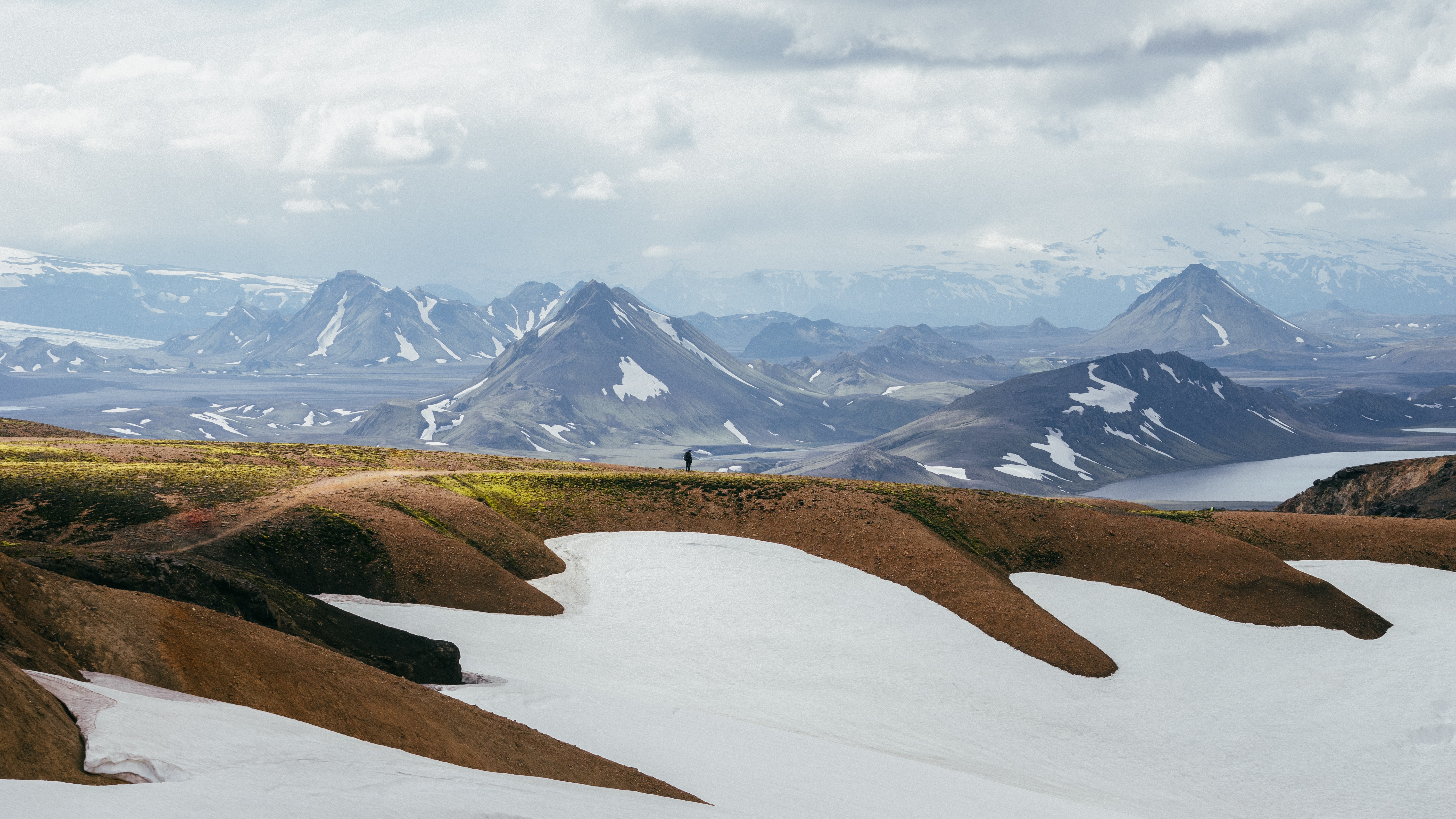 A person in the distance stands on a ridge and looks out at snowy mountains