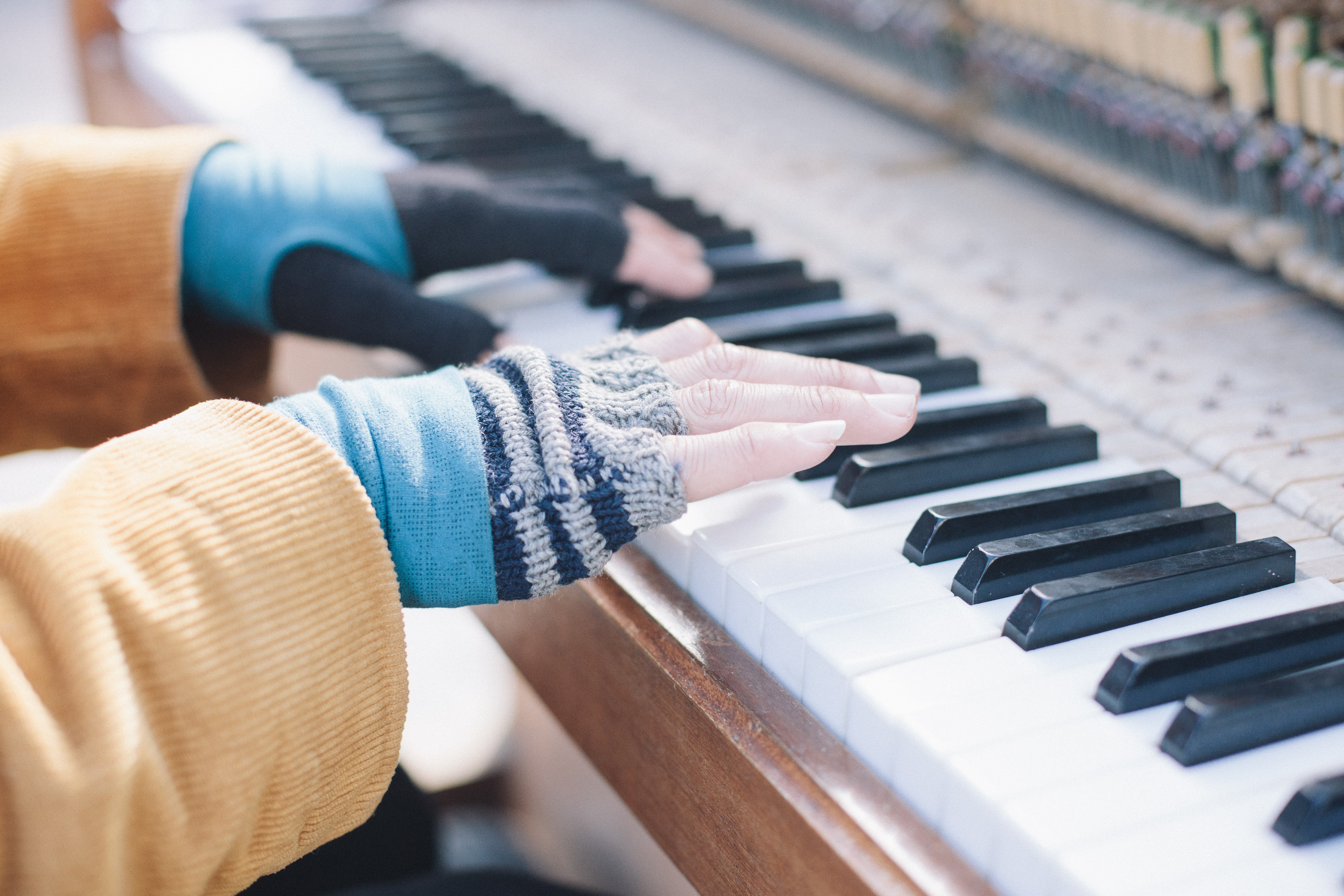 A person in fingerless gloves playing the piano in daylight