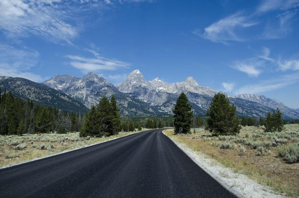 gray asphalt road under blue sunny sky