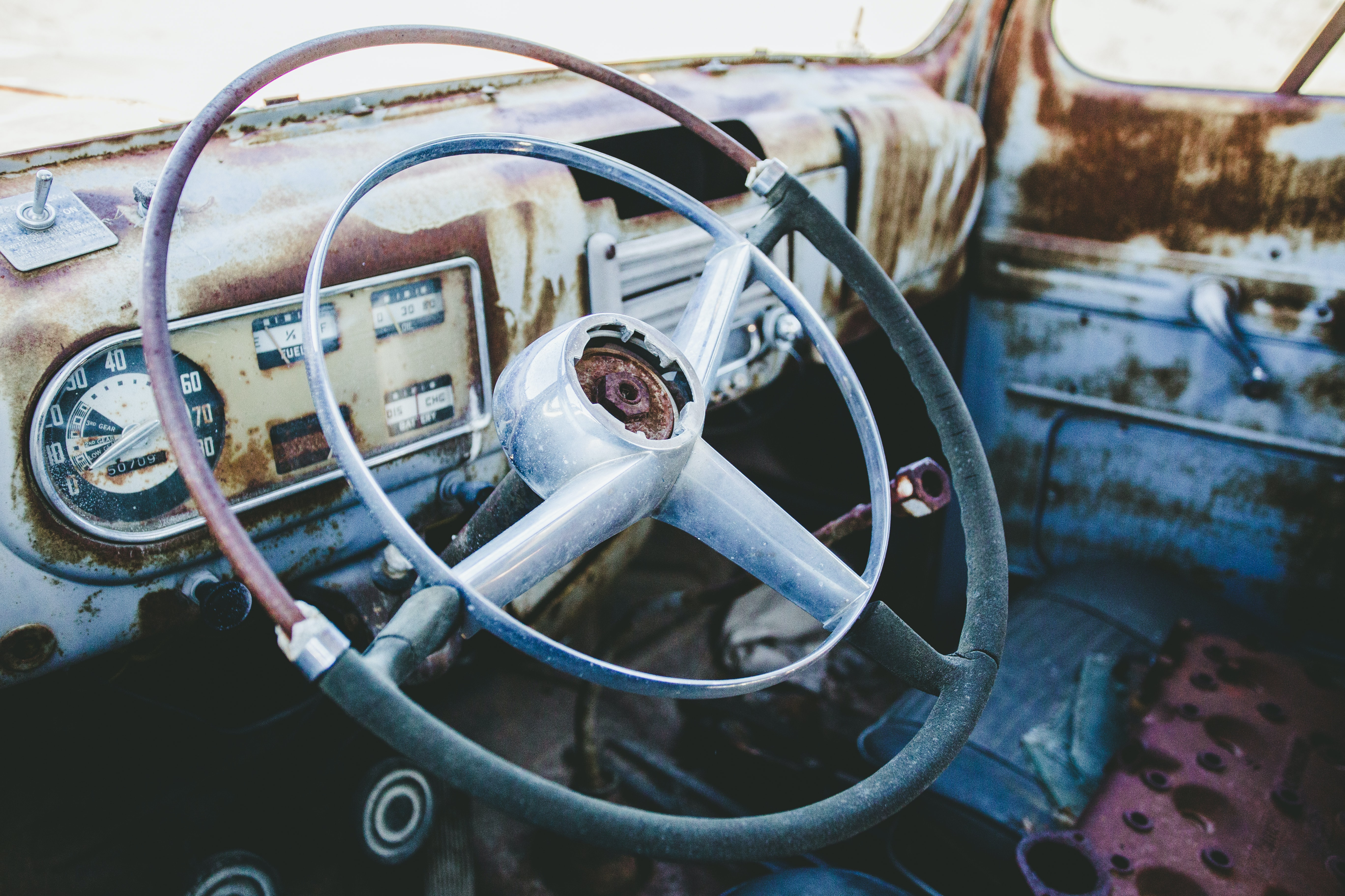 Steering wheel and speedometer in a rusty, abandoned classic car