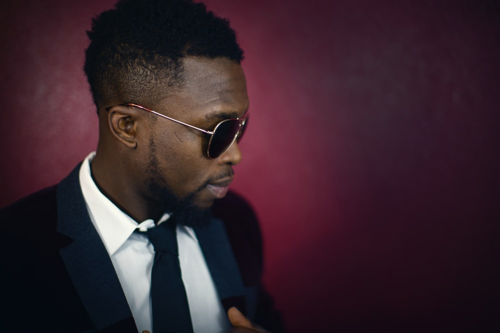 An elegant man in sunglasses against the backdrop of a dark red wall