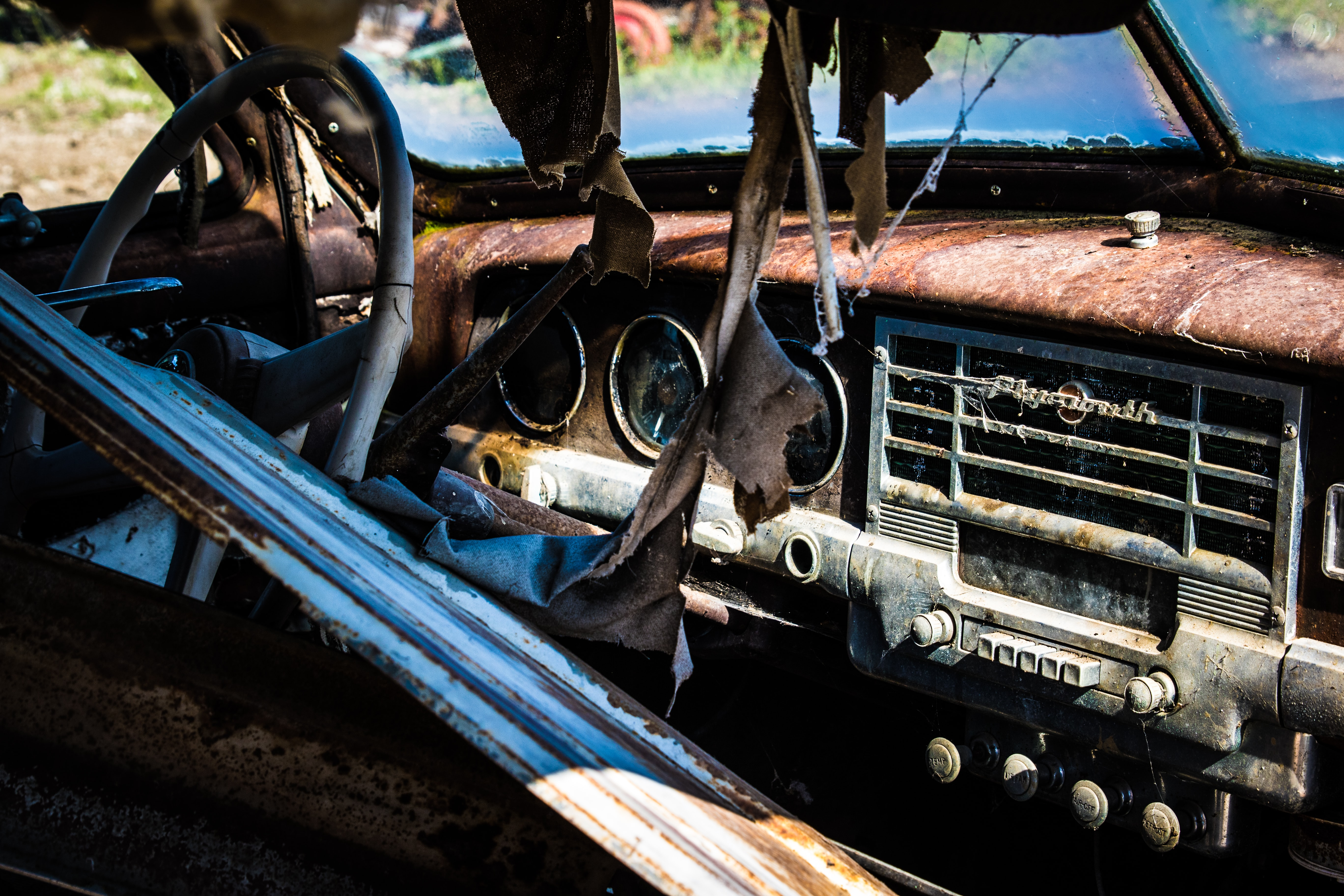 Close up shot passenger seat of a rusty Plymouth, including steering wheel, dashboard, eight-track cassette player