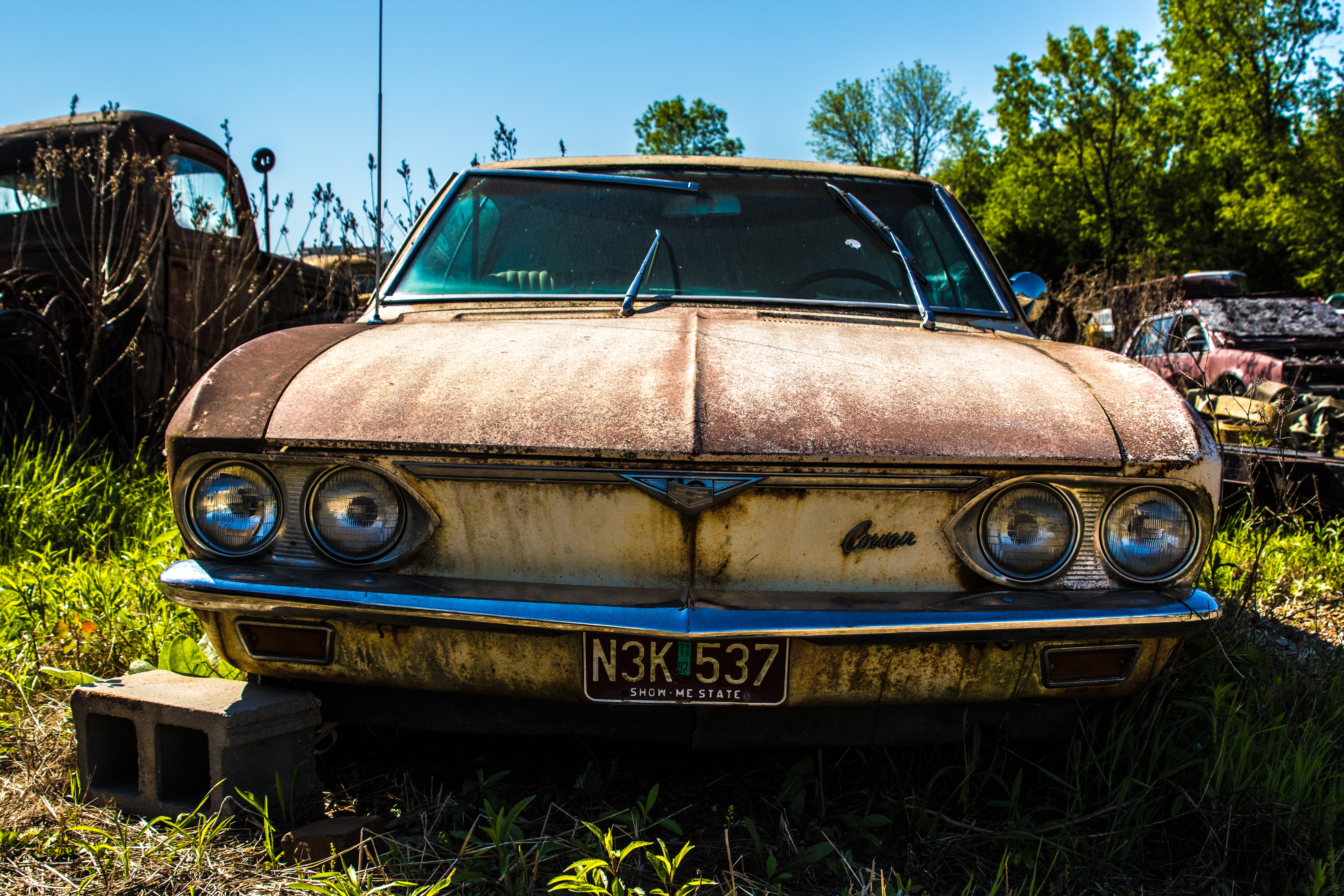 Front of a rusty, abandoned Fender with a license plate and headlights in a car junkyard