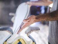 A blurry shot of a man's hands holding a handmade part of a surfboard