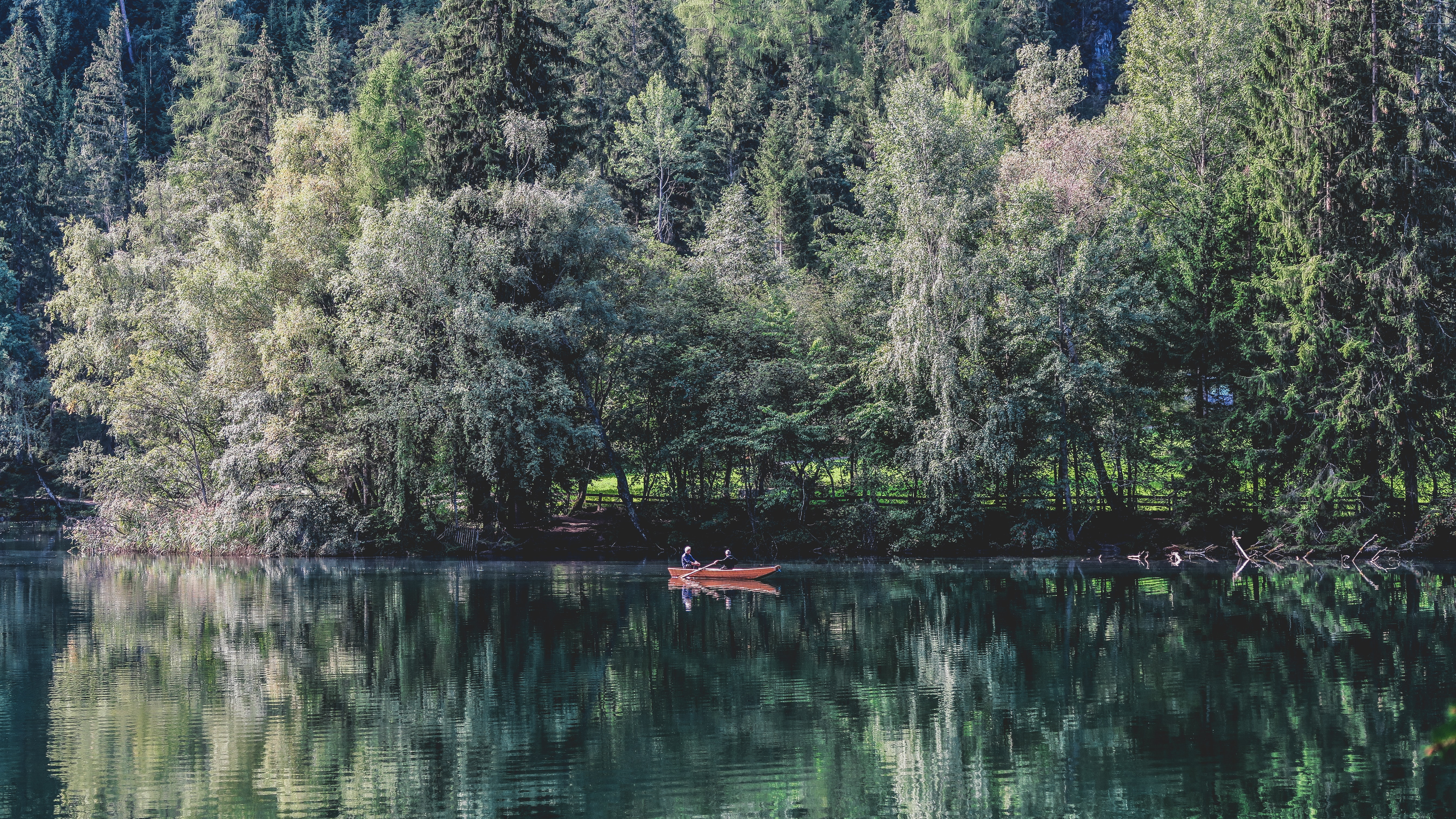 two people on red boat on water near trees during daytime