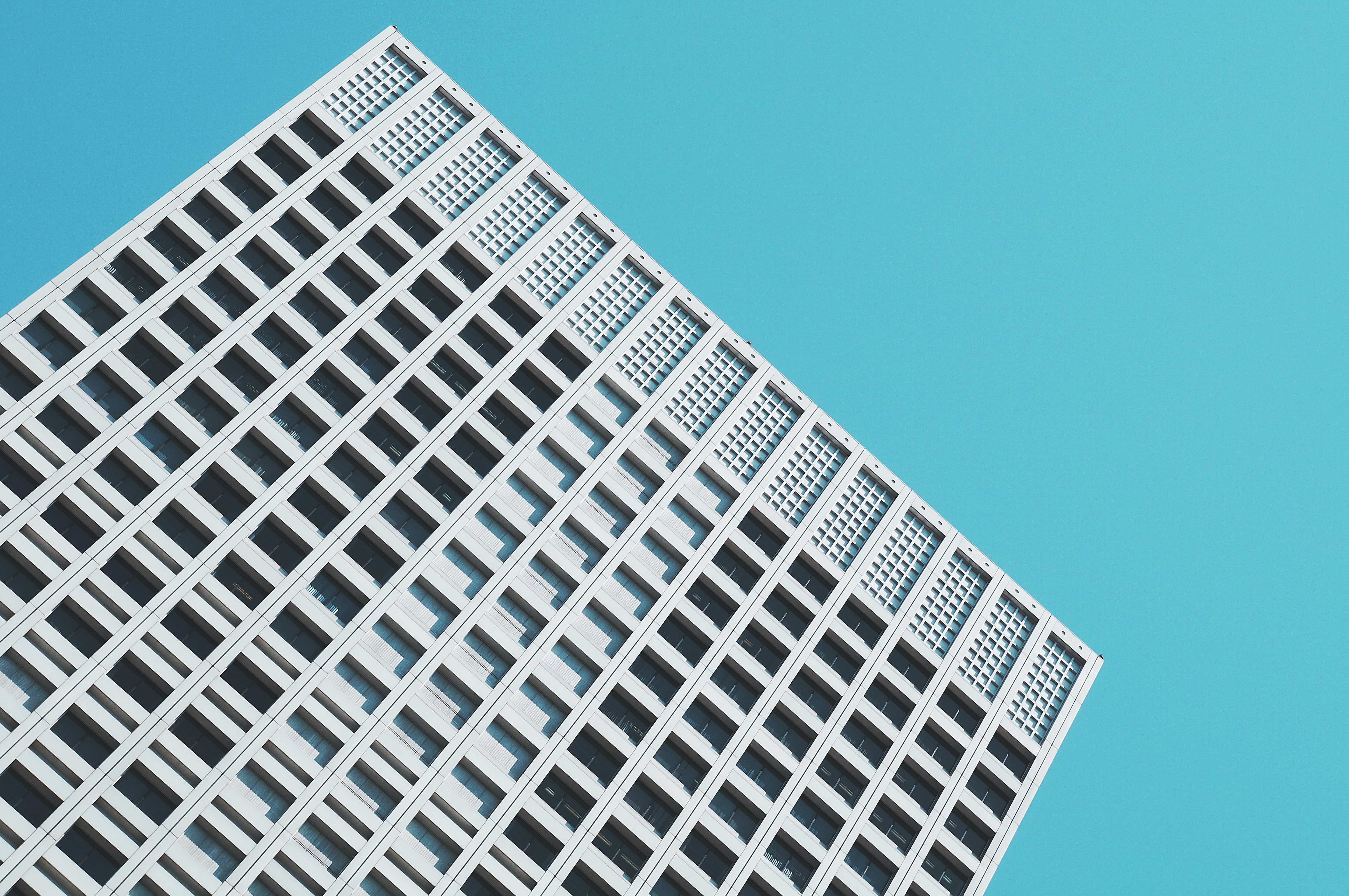 A minimalist concrete skyscraper building with many windows stands at an angle under blue sky
