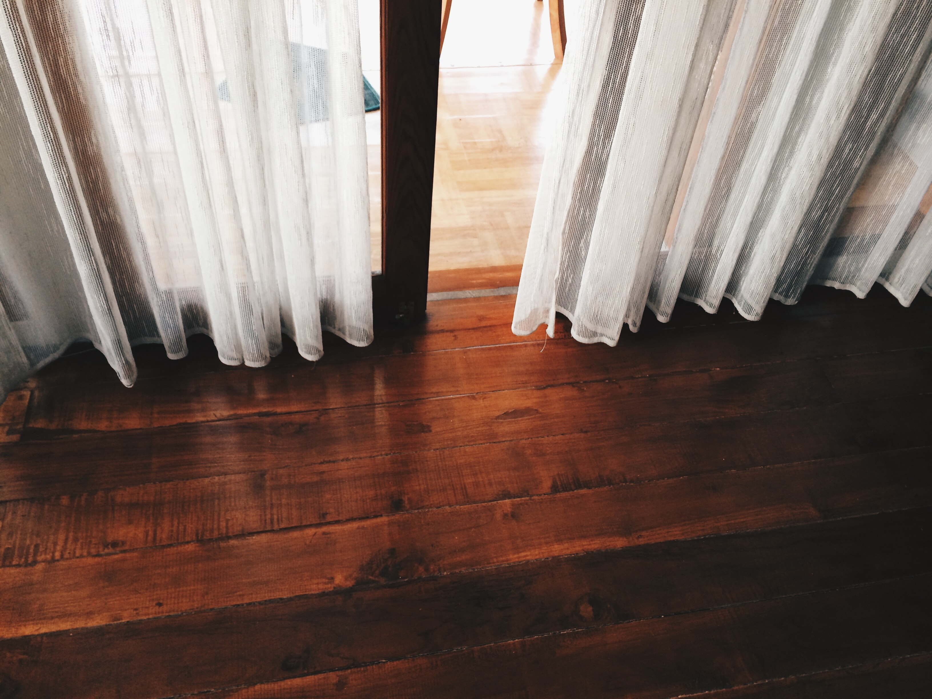 A hard wood floor in a house with the bottoms of sheer white curtains