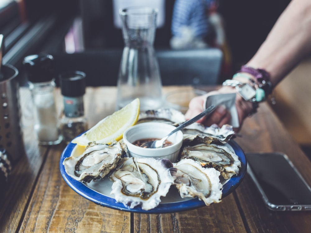 Waiter serves a plate of fresh oysters