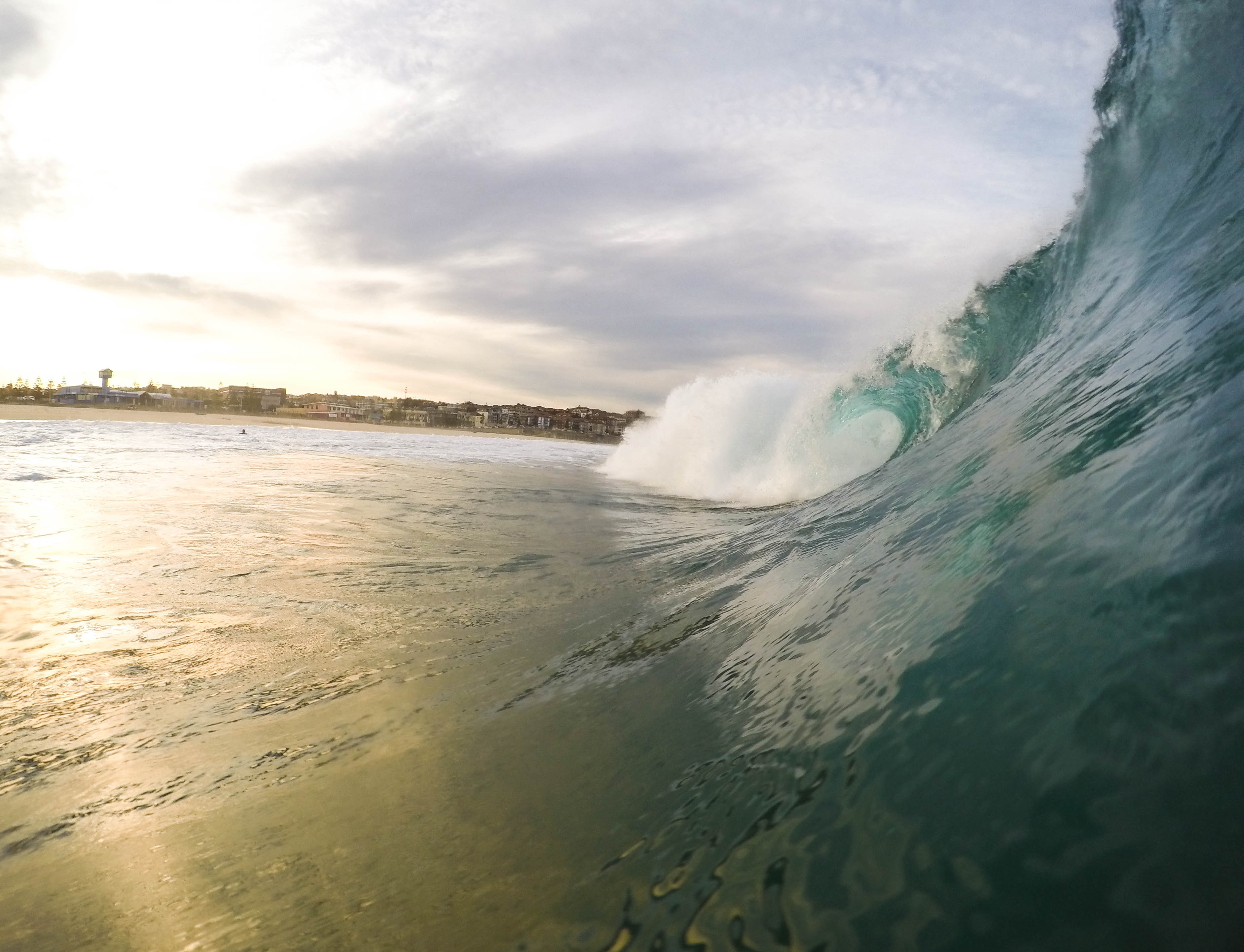 A large wave coming in during the early evening sunset.