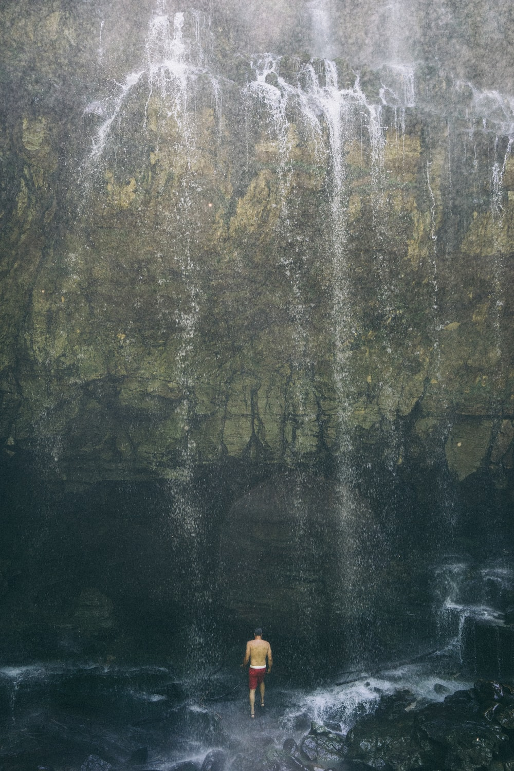 man standing underneath waterfall
