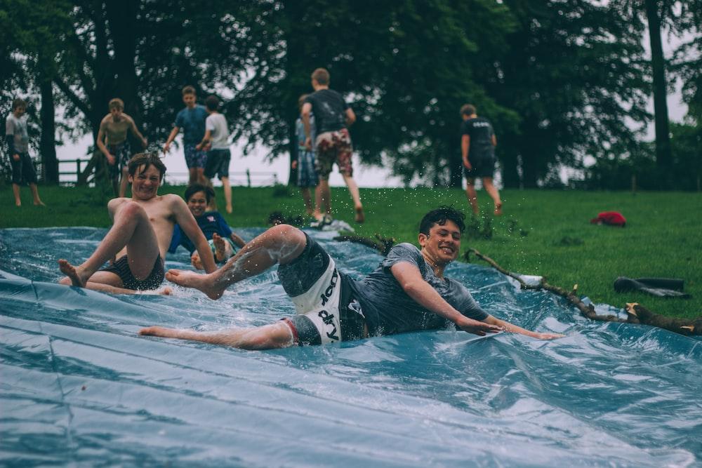 group of men sliding on blue canopy