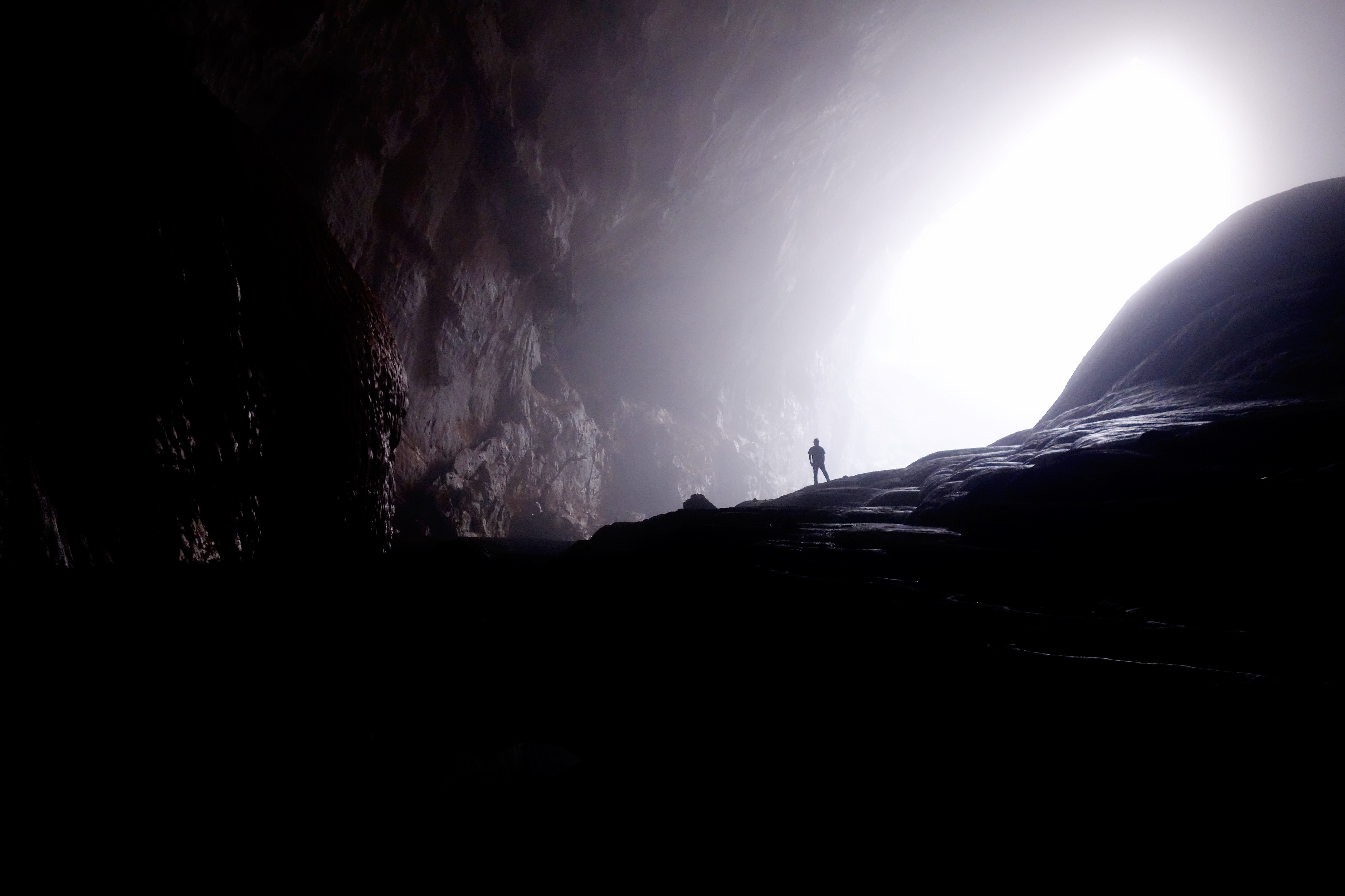 A silhouette of a man at the entrance to an enormous cavern