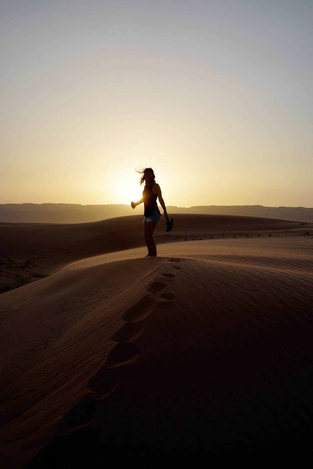woman standing on sand during sunset