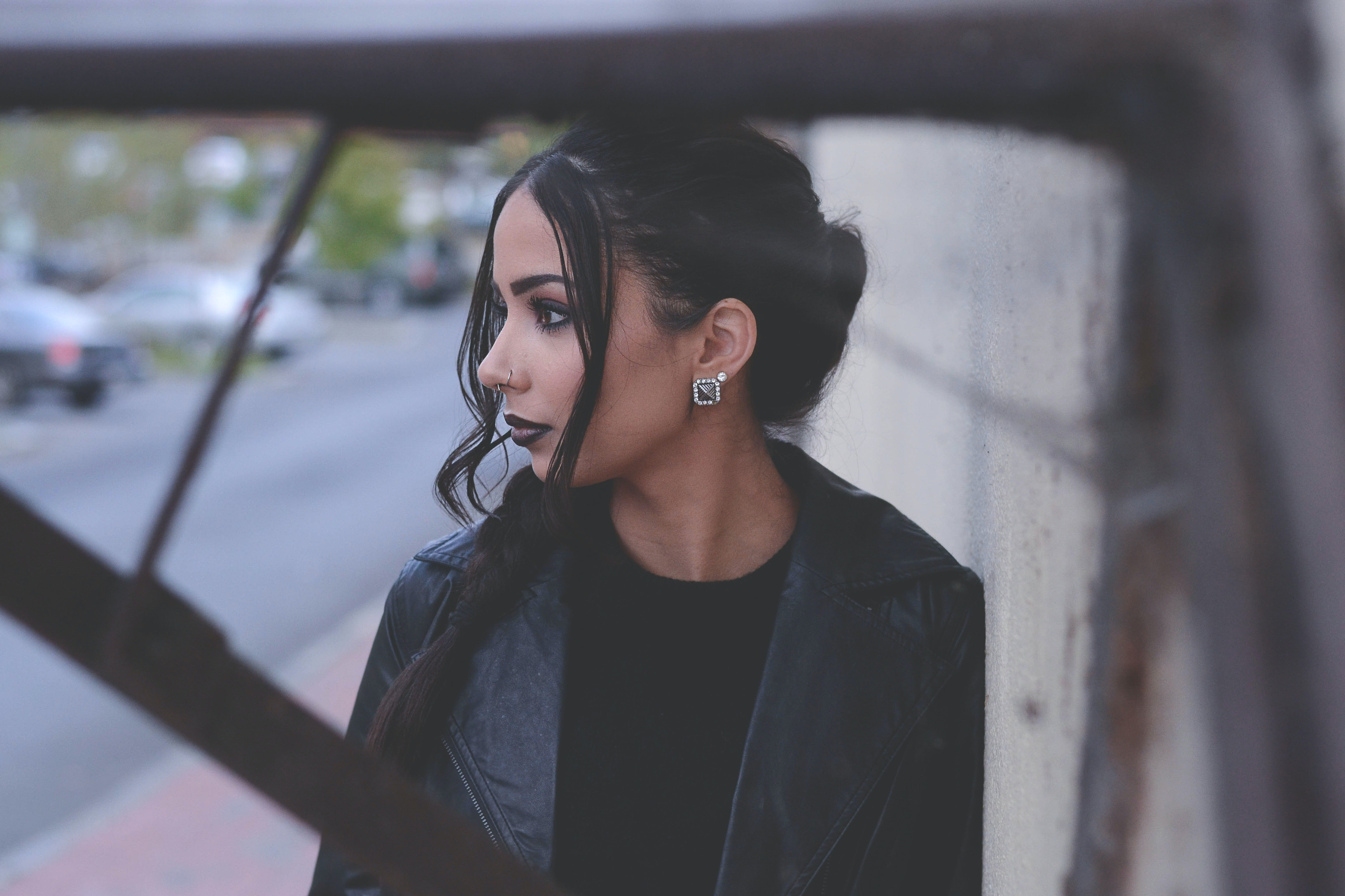 Fashionable woman with dark makeup and hair leaning against a wall
