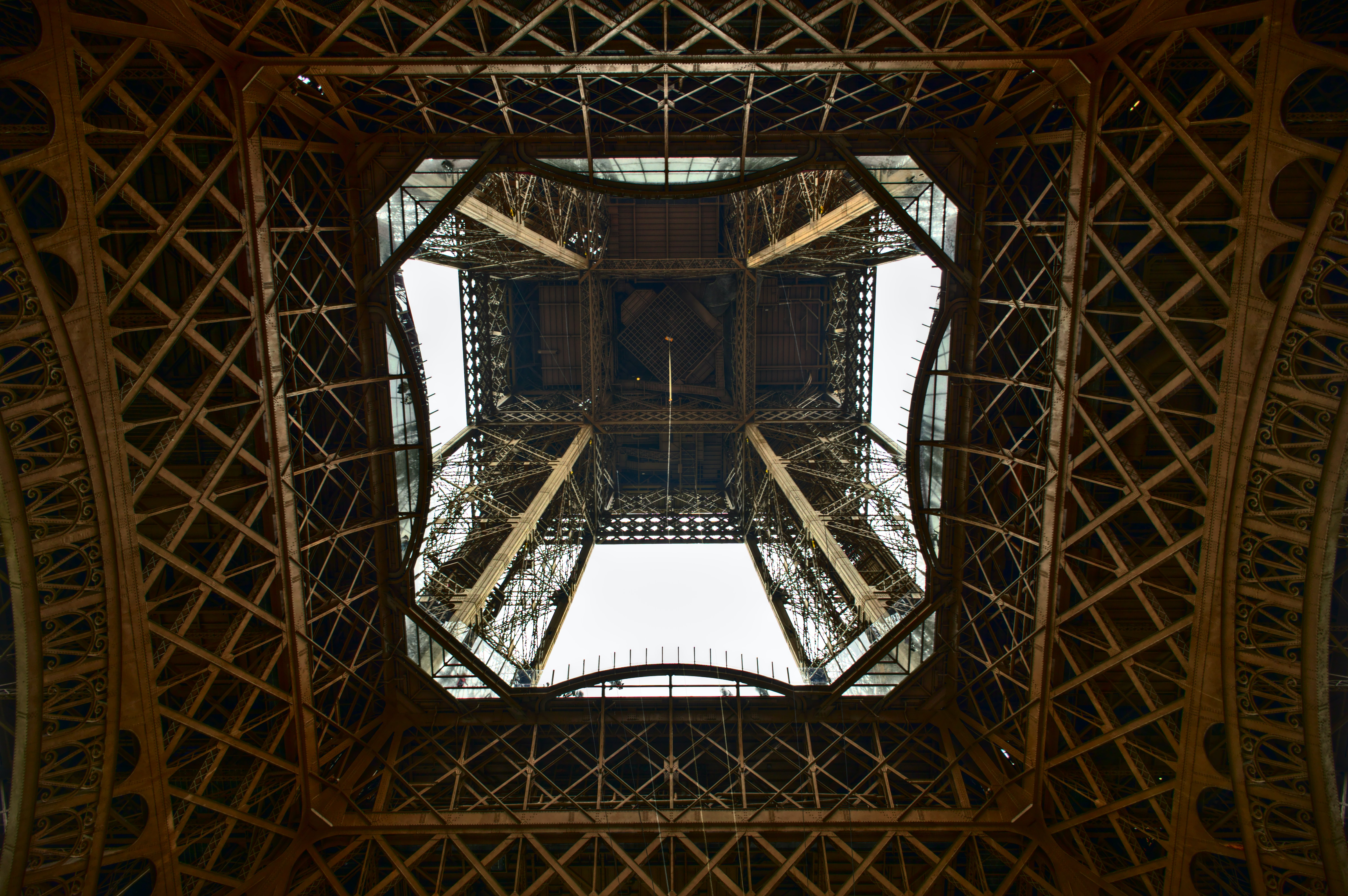 Looking up at the frame of the Eiffel Tower in Paris from directly underneath it