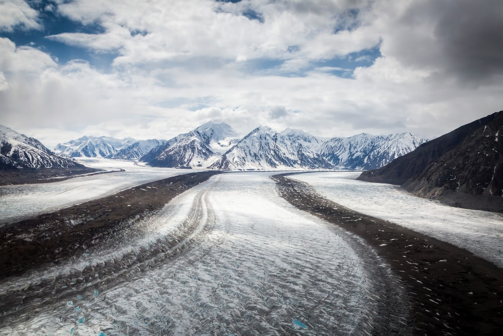 A road filled with snow patches looking towards snow covered mountains and cloudy skies in Yukon Territory.