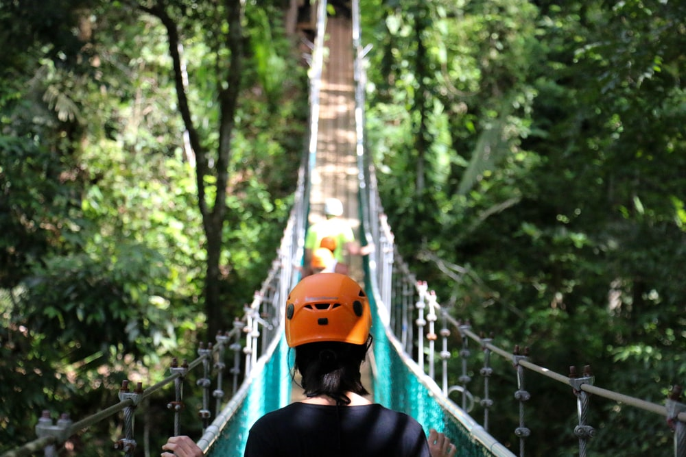 woman crossing hanging bridge during day