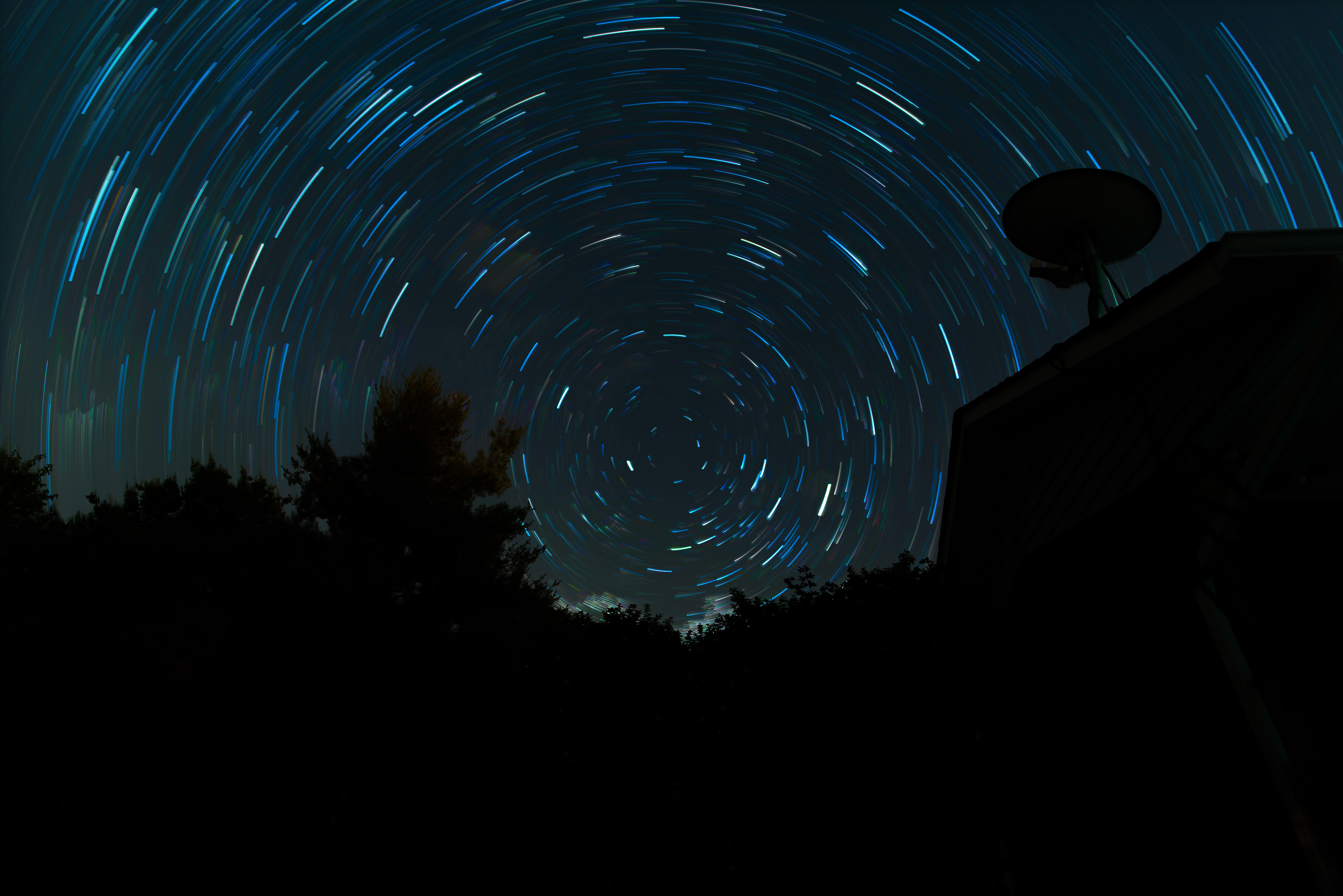 Star trail above the silhouette of trees and rooftop