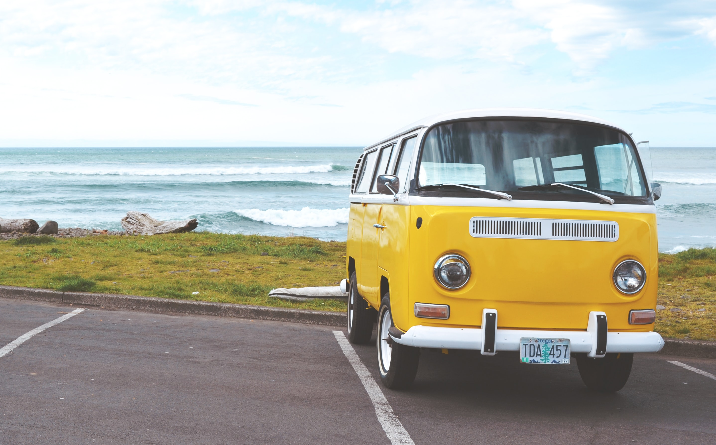 A white and yellow Volkswagen bus in a parking lot by the seaside