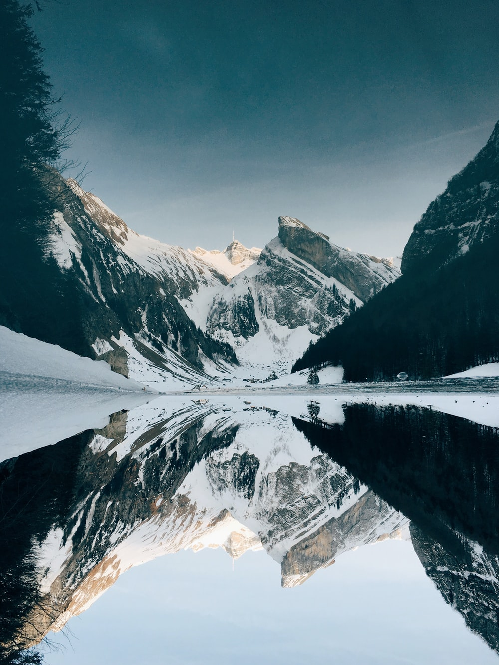 snow-covered mountain near lake under blue sky
