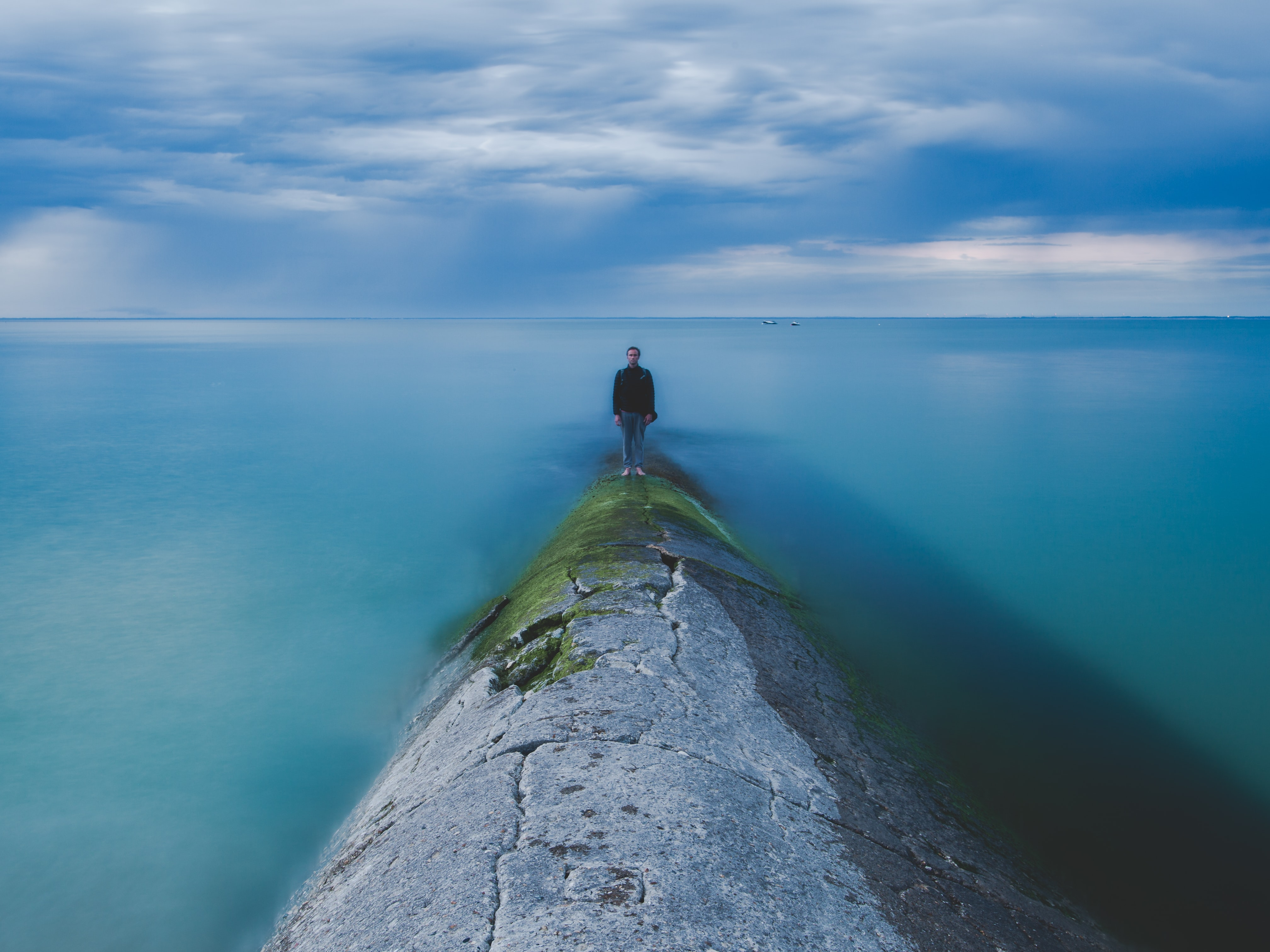 A man standing on a barrier just above the sea in Phare des Baleines