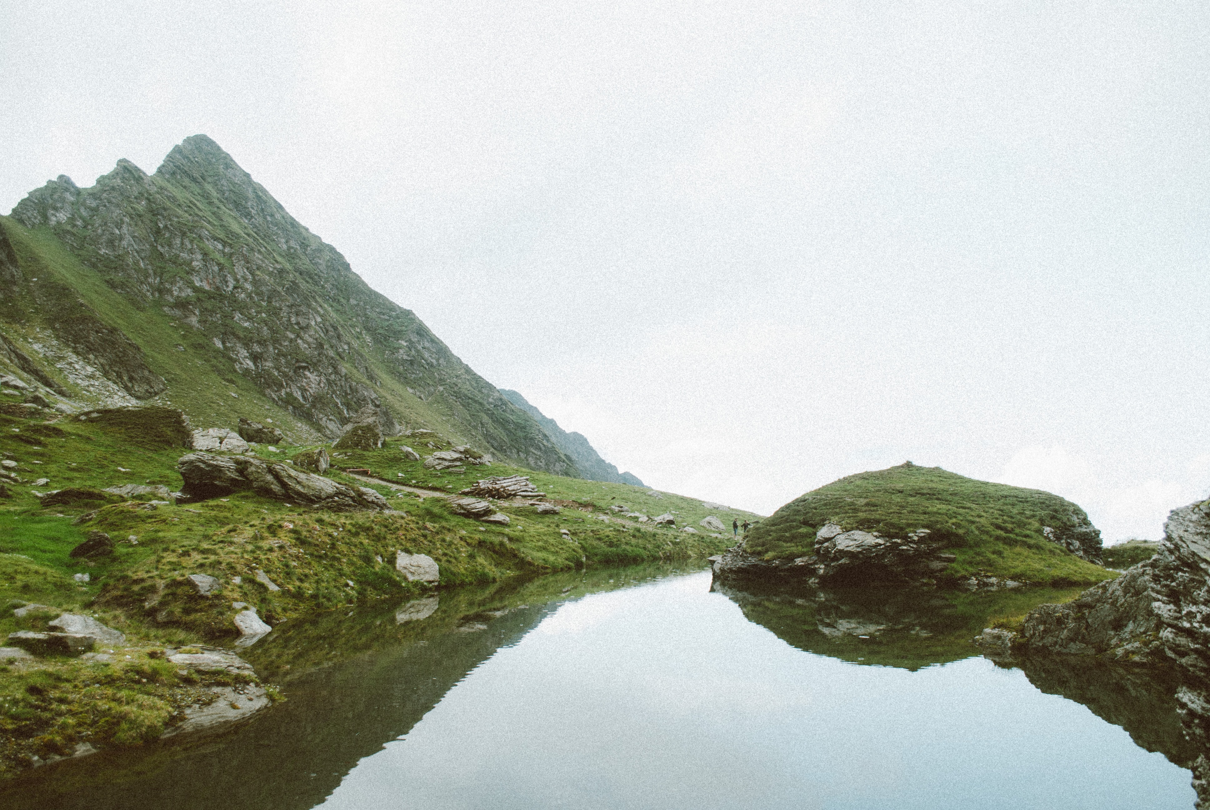 Reflective water by a grassy hillside on a foggy day