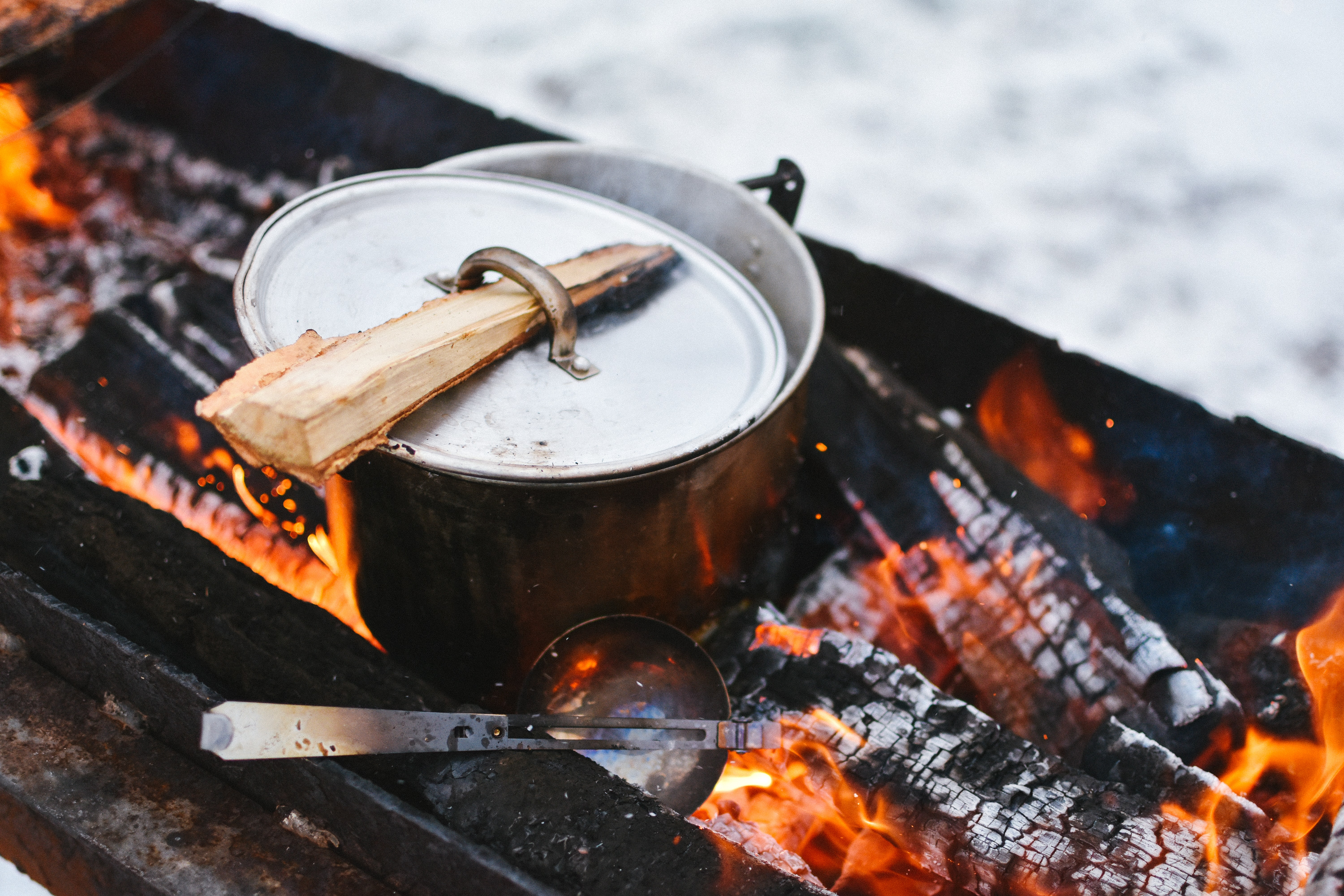 A metal pot sitting in a wood firepit with a log used to pick up the hot lid
